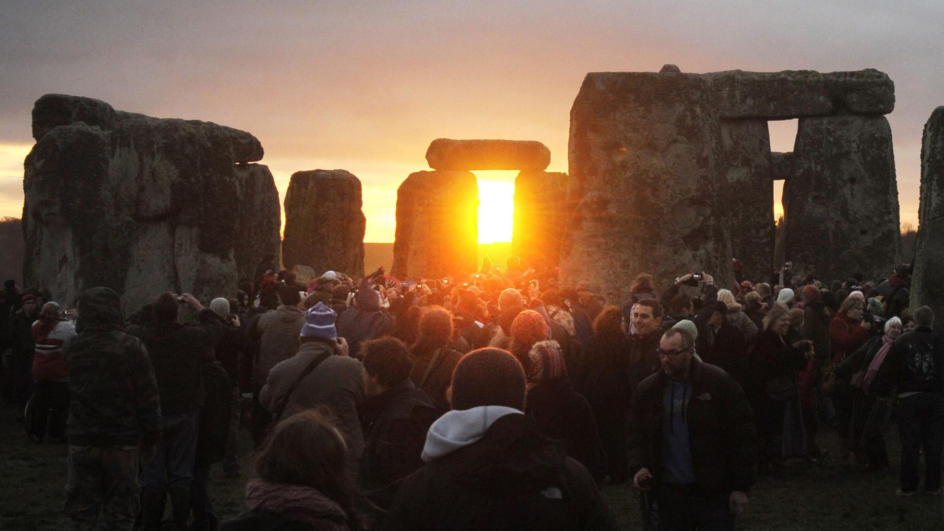 ALTERNATIVE CROP LON816 - People watch the sunrise at the northern Winter Solstice celebration at Stonehenge in Wiltshire, Thursday, Dec. 22, 2011. The omens are good that 2012 will be an excellent year, a druid said today, after the sun shone on Stonehenge during a dawn ceremony to mark the winter solstice. One of the most famous sites in the world, Stonehenge is composed of a circular setting of large standing stones set within earthworks, believed to be thousands of years old. .  (AP Photo/Tim Ireland/PA) UNITED KINGDOM OUT  NO SALES  NO ARCHIVE