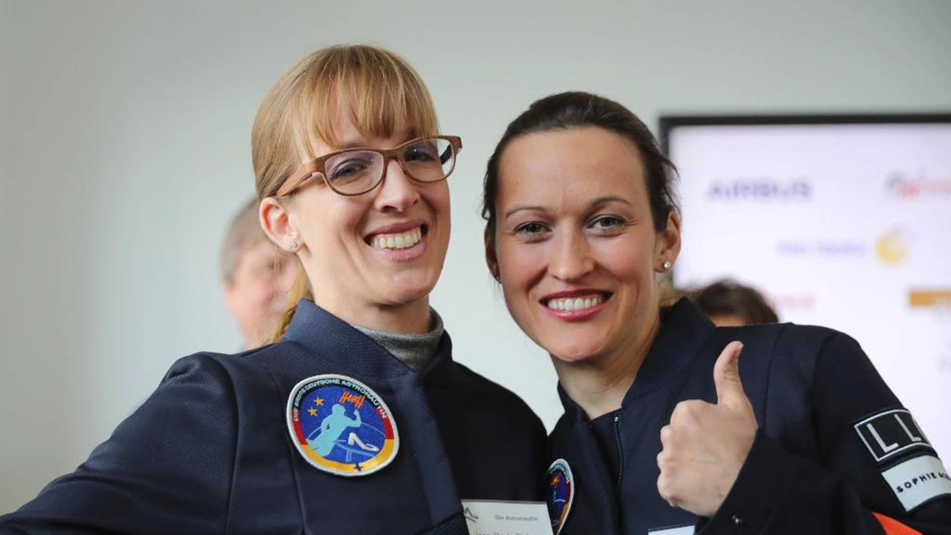 Insa Thiele-Eich, left, and  Nicola Baumann give a thumb up sign in Berlin, Wednesday, April 19, 2017. A fighter pilot and a meteorologist have made the finals in the race to become Germany's first female astronaut. A panel of experts picked the two finalists - German air force Eurofighter jet pilot Maj. Nicola Baumann and meteorologist Insa Thiele-Eich - from the top six candidates.  (Michael Kappeler/dpa via AP)