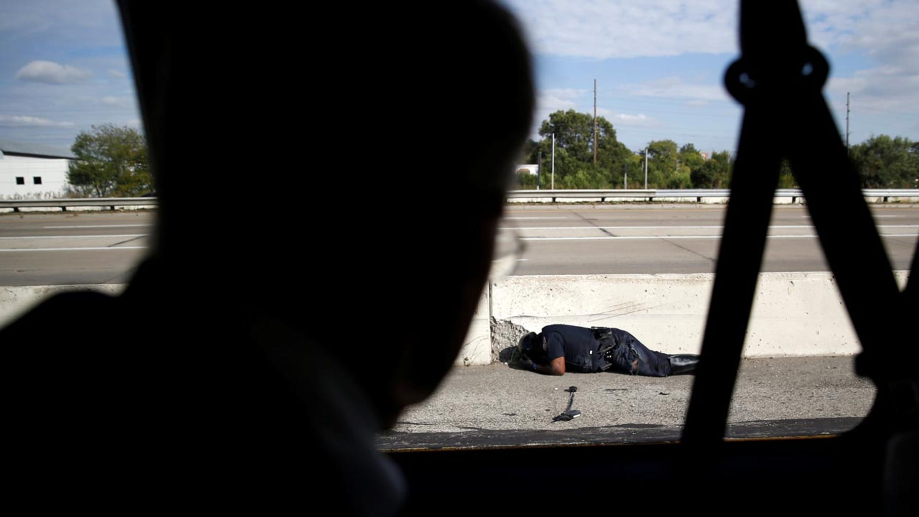 A police officer involved in an accident lies on the ground as President Trump's motorcade travels past him in Indianapolis, Sept. 27, 2017.