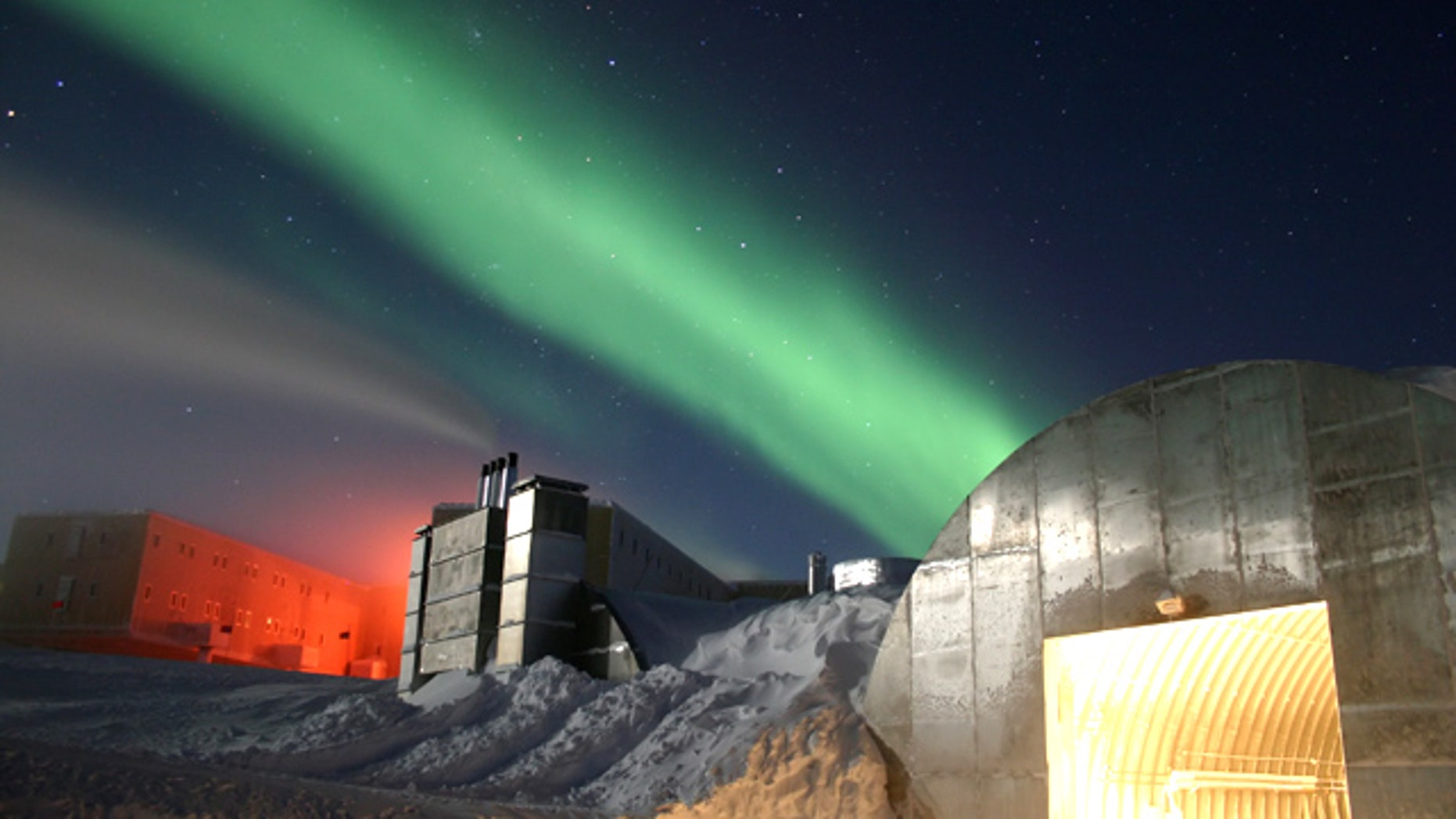 Amundsen-Scott South Pole Station during the long Antarctic night, with a new station at far left, power plant in the center and the Aurora Australis dancing through the sky.
