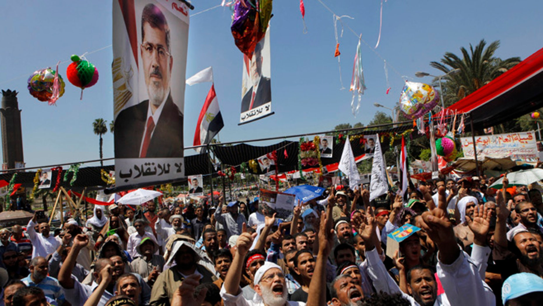 Supporters of Egypt's ousted President Mohammed Morsi shout slogans under his posters following Friday prayers in Nahda square, where protesters installed their camp near Cairo University in Giza, southwest of Cairo, Egypt, Friday, Aug. 9, 2013.