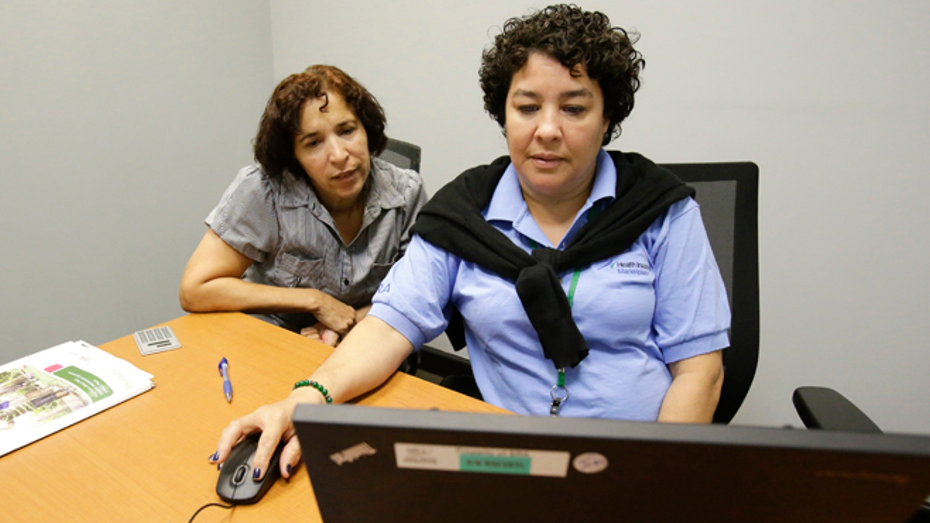 FILE - In this Nov. 17, 2014 file photo, Maria Arias, left, gets help from navigator Yvette Frias, as she signs up for the Affordable Care Act at the Orlando Enrollment Assistance Center, in Orlando, Fla. Florida has eclipsed California to become the state with the highest number of consumers buying health coverage through new insurance markets under the Affordable Care Act, according to federal statistics released Wednesday, Feb. 18, 2015. (AP Photo/John Raoux, File)