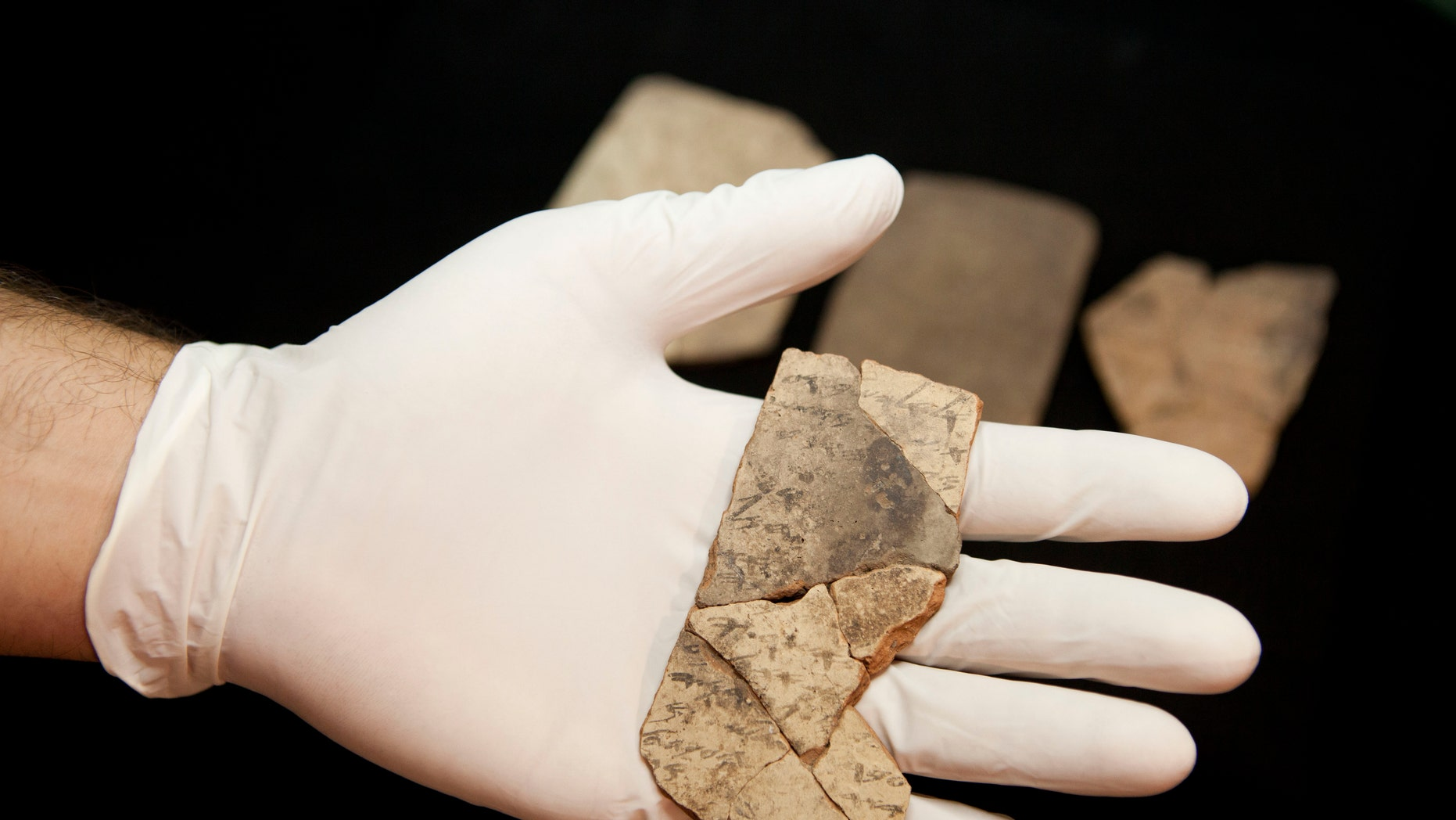 Letters inscribed on pottery, known as ostracons, which were unearthed in an excavation of a fort in Arad, Israel, and dated to about 600 B.C. shortly before Nebuchadnezzar's destruction of Jerusalem, are seen in Israel Museum in Jerusalem Tuesday, April 12, 2016. (AP Photo/Dan Balilty)