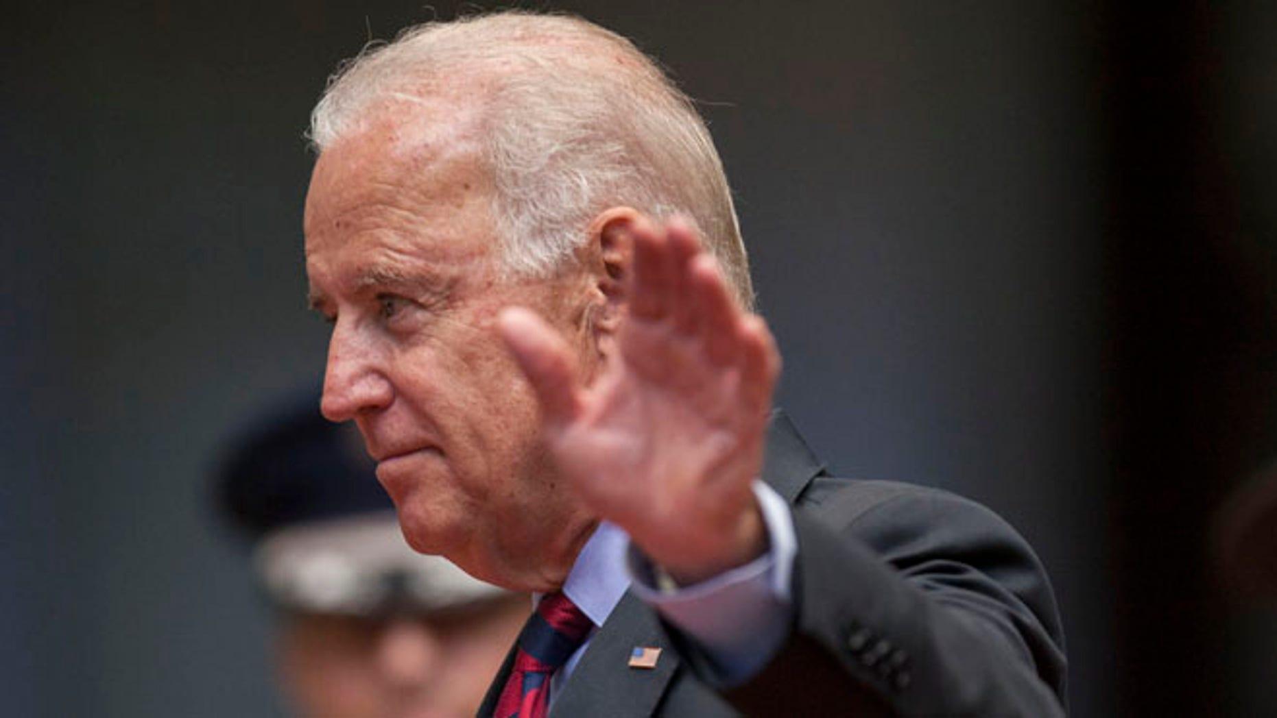 U.S. Vice President Joe Biden waves to photographers at the National Palace in Guatemala City, Friday, June 20, 2014.