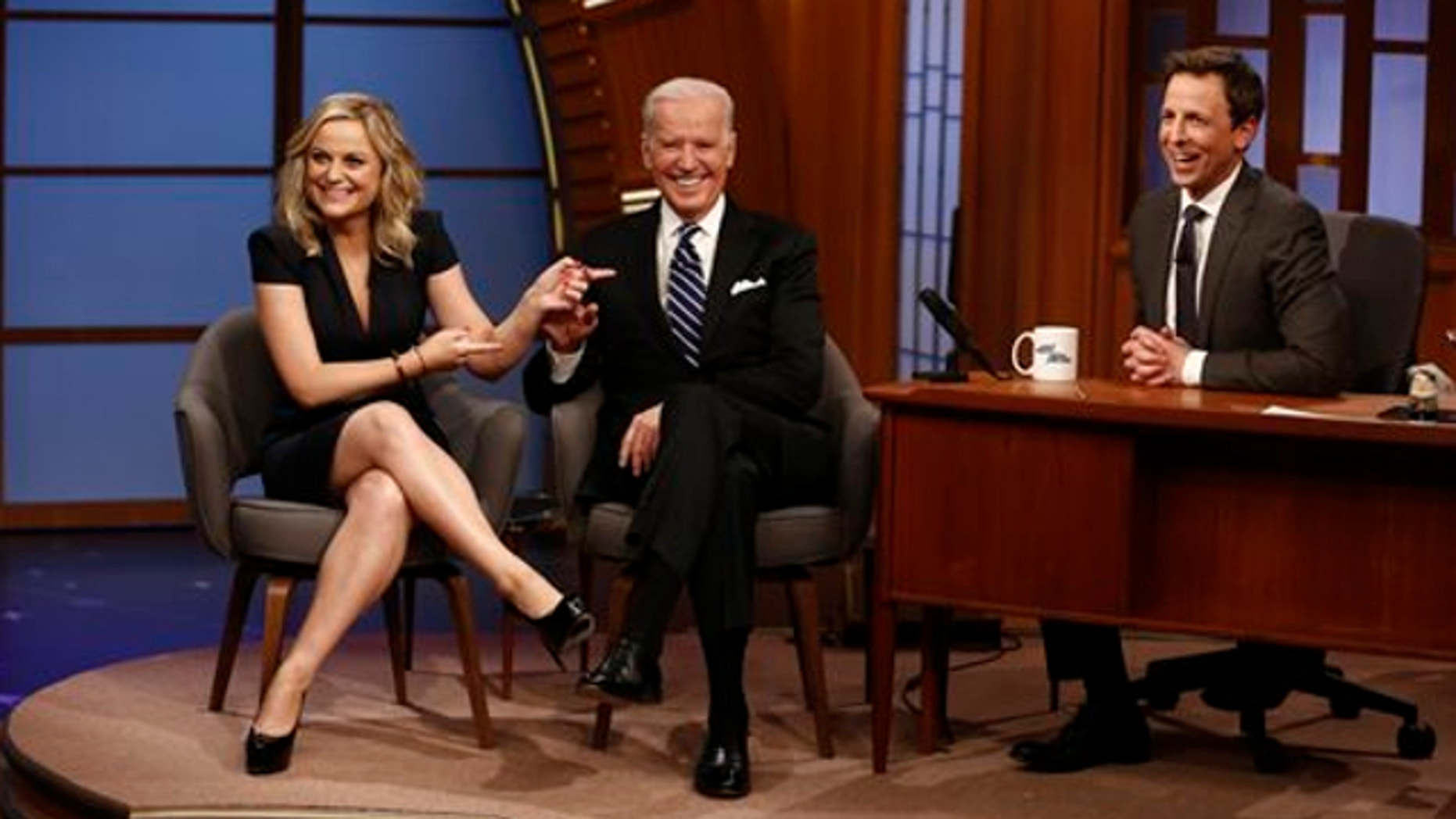 "Feb. 24, 2014: In this photo provided by NBC, from left, actress Amy Poehler and Vice President Joe Biden appear with host Seth Meyers on the premiere of ""Late Night with Seth Meyers"" in New York."