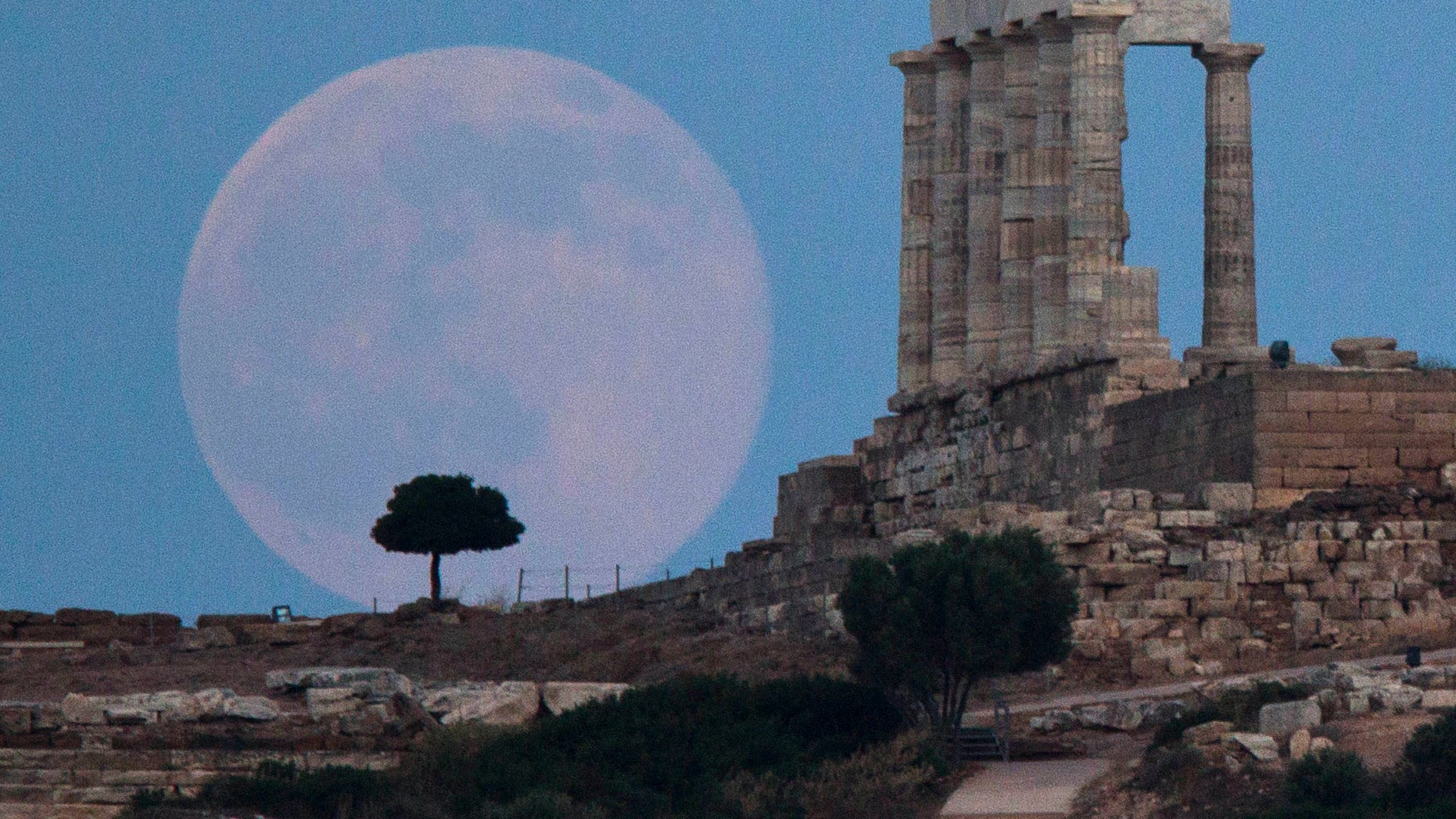 The full moon rises behind a tree next to the ruins of the ancient Temple of Poseidon near Athens, Greece.