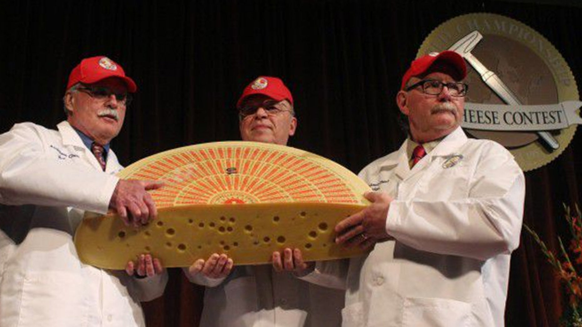 March 19, 2014: Three judges for the 2014 World Championship Cheese Contest hold the champion, a Swiss Emmentaler.