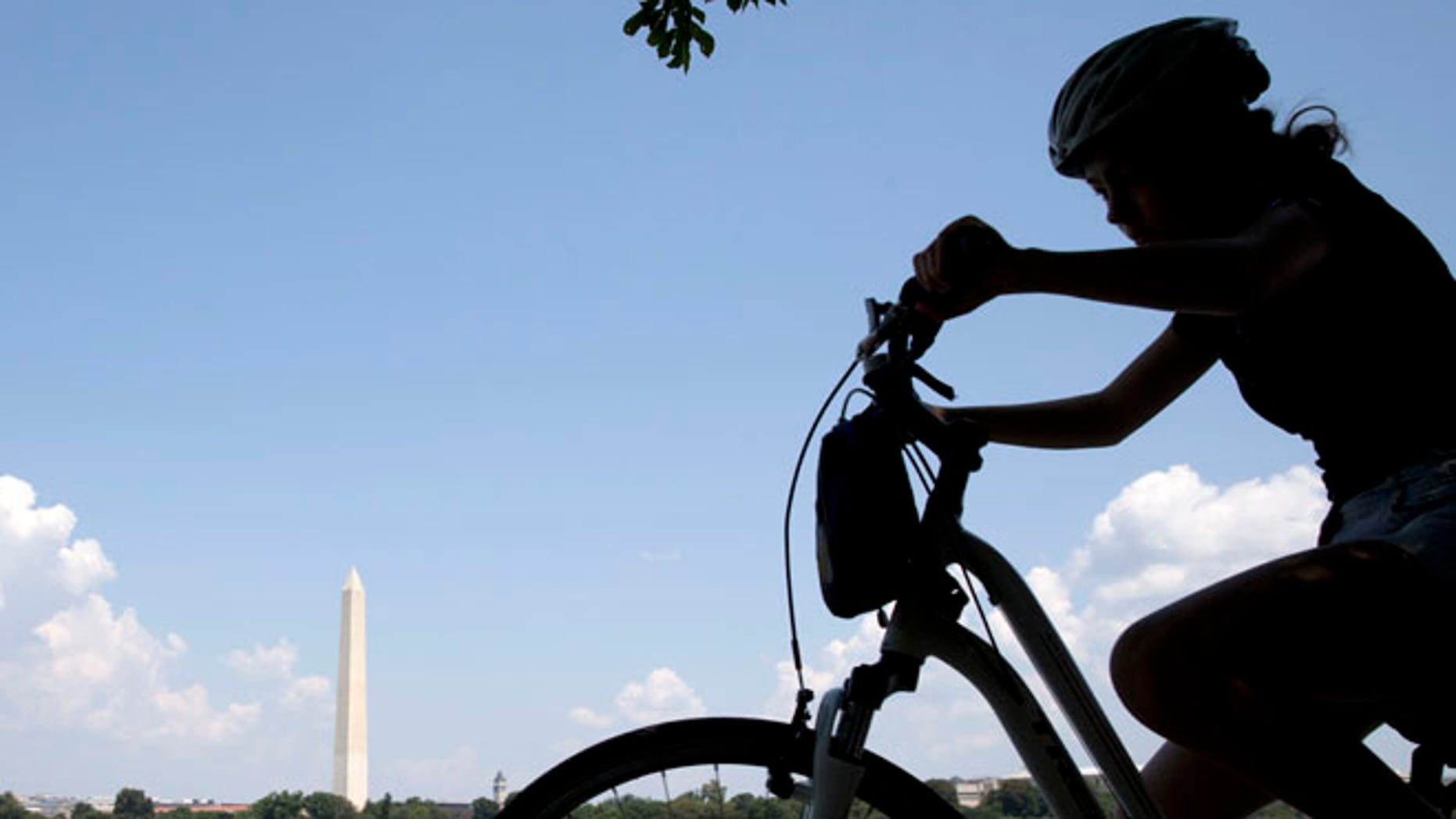 Aug. 17, 2015: A girl on a bicycle pedals around the Tidal Basin with the Washington Monument in the background.