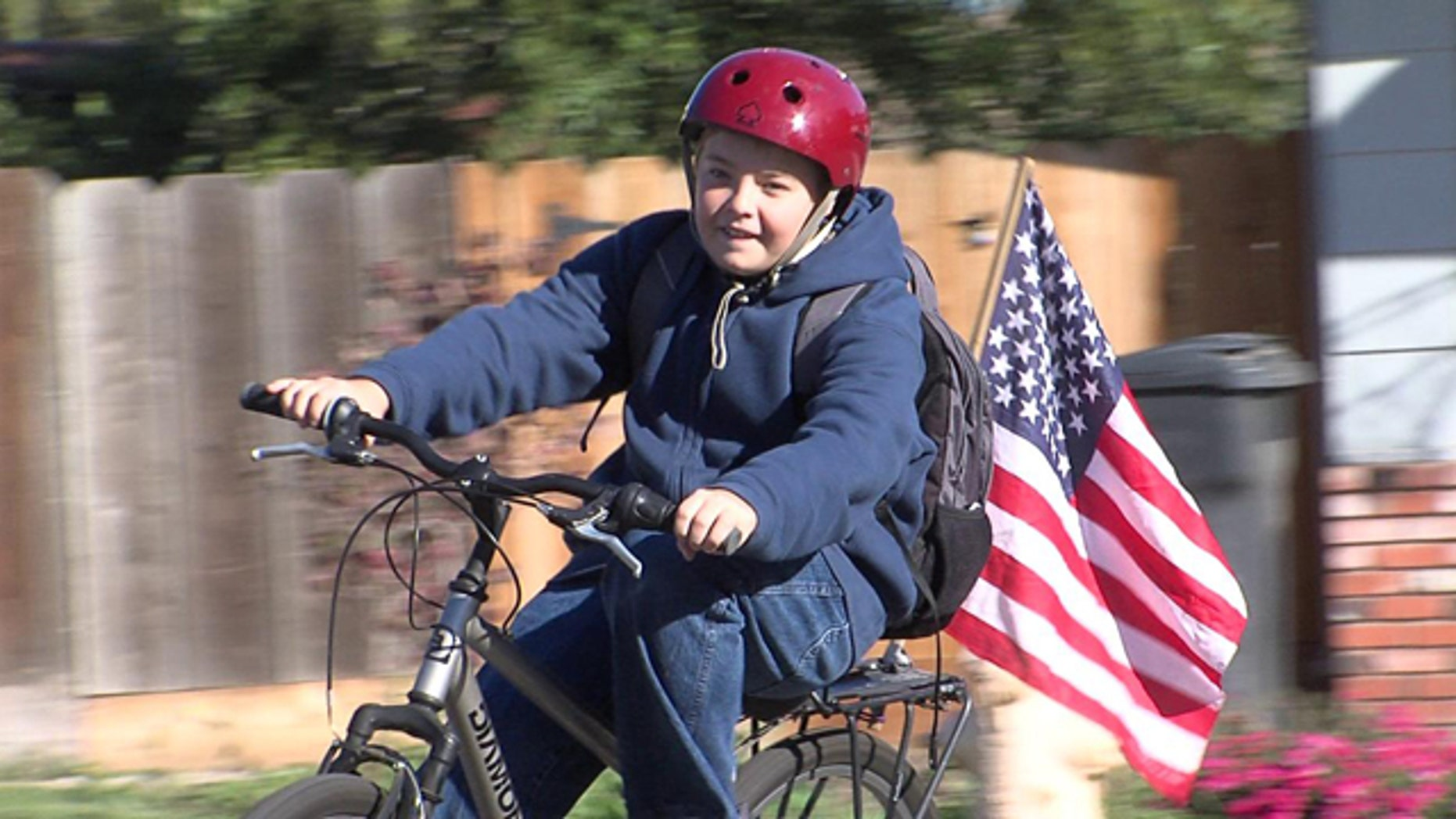 Cody Alicea, 13, rides his bicycle with his American Flag attached.