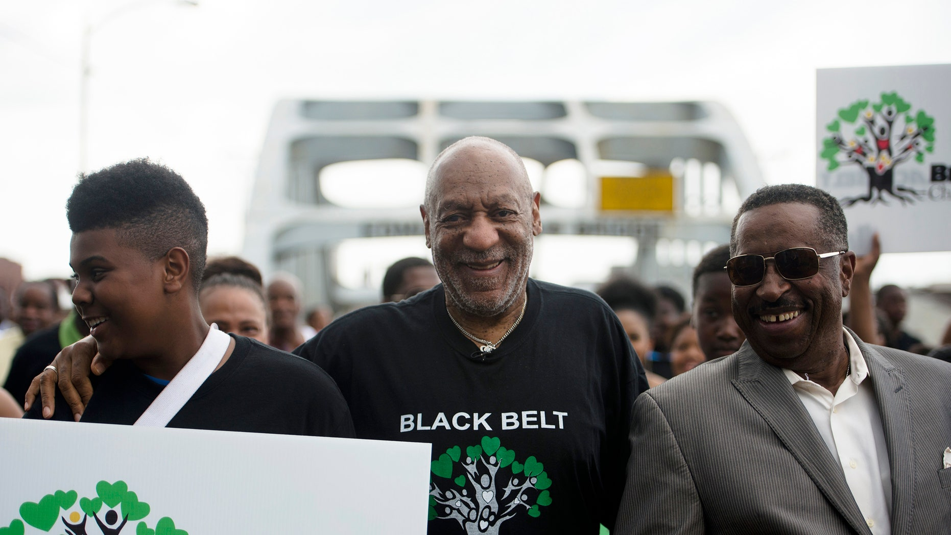 """May 15, 2015. Bill Cosby, center, walks over the Edmund Pettus Bridge with Nysean Perkins, left, and Gregory Calhoun, Friday, May 15, 2015, in Selma, Ala. The march was arranged by The Black Belt Community Foundation as part of their """"Black Belt Children Matter"""" campaign."""