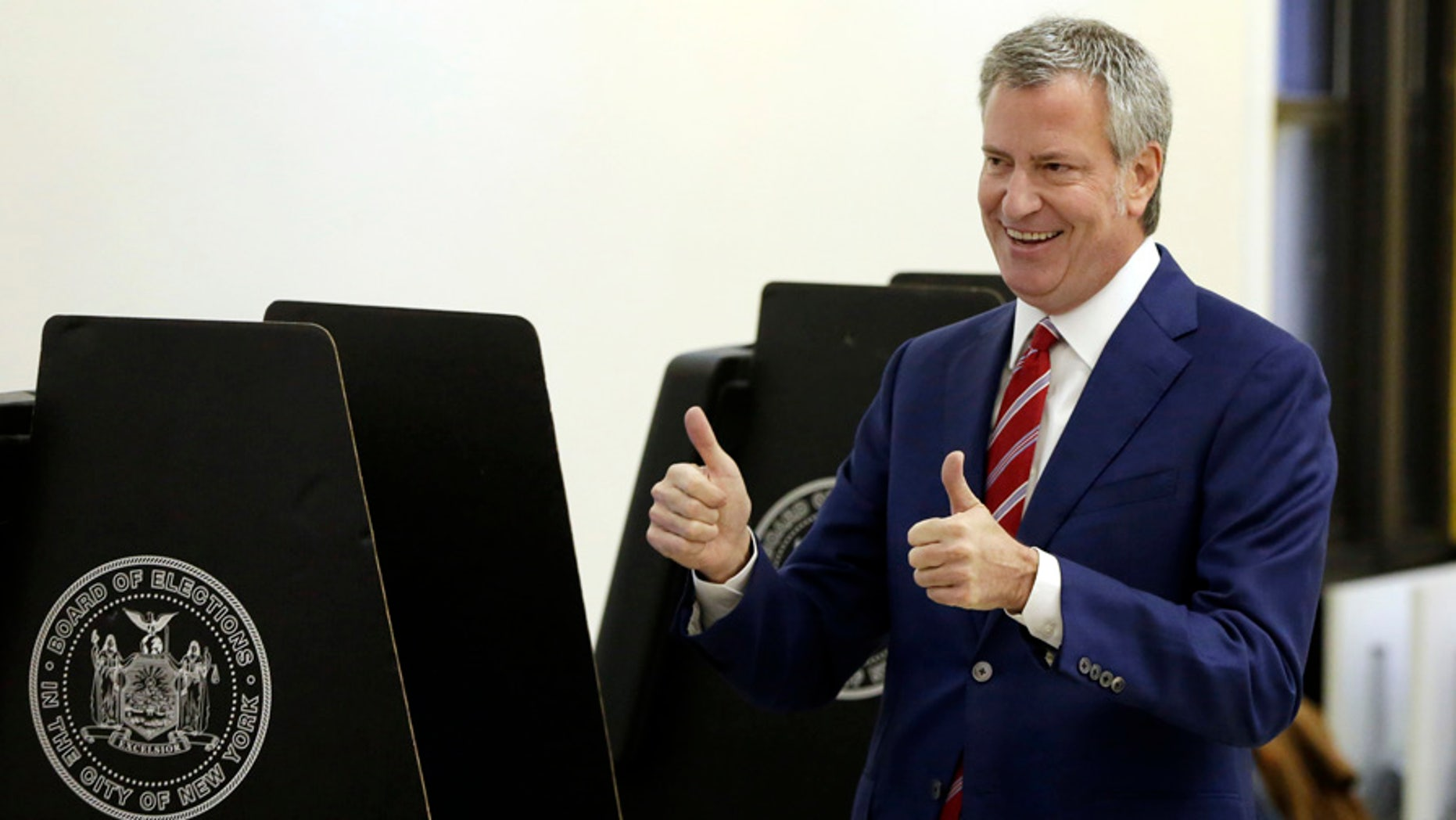 In this Nov. 7, 2017 photo, New York Mayor Bill de Blasio signals a double thumbs-up after voting at the Park Slope Library, in the Brooklyn borough of New York.