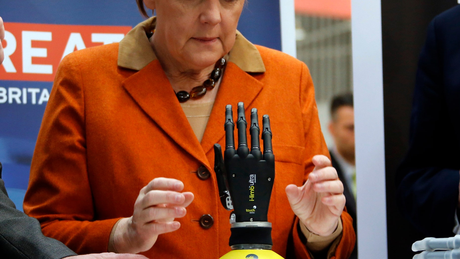 File photo: German Chancellor Angela Merkel looks at a bionic hand during a tour at the CeBIT technology fair in Hanover March 10, 2014. (REUTERS/Fabrizio Bensch)