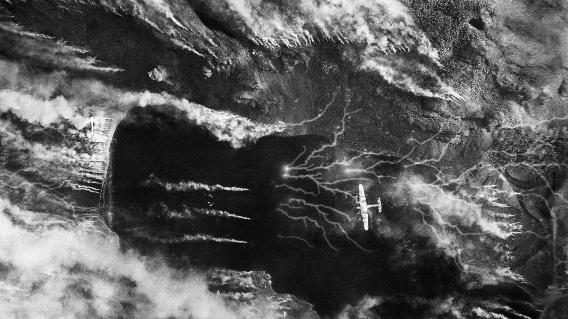 The Germans release a colossal smoke screen in an effort to hide their battleship Tirpitz, moored in Kaa Fjord, Norway, as it's attacked by a Lancaster on Sept. 15, 1944. (Credit: No. 5 Group RAF/IWM)