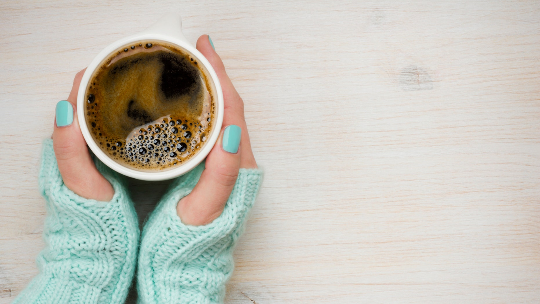 Female hands holding a coffee mug in knitted mittens