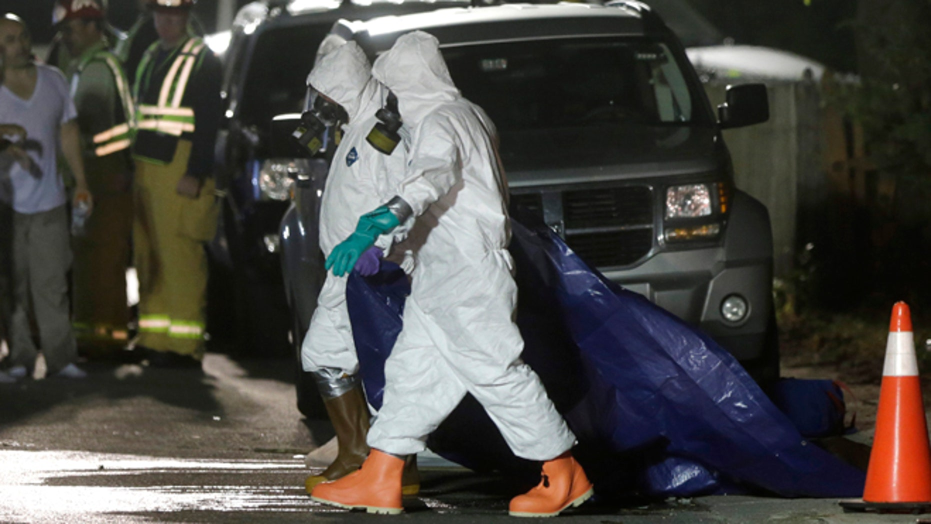 Sept. 11, 2014: Investigators in protective clothing drag a tarp across the street in front of a house where a Massachusetts prosecutor said the bodies of three infants were found in Blackstone, Mass. Worcester County District Attorney Joseph Early Jr. said Thursday authorities don't know when or how the babies died.