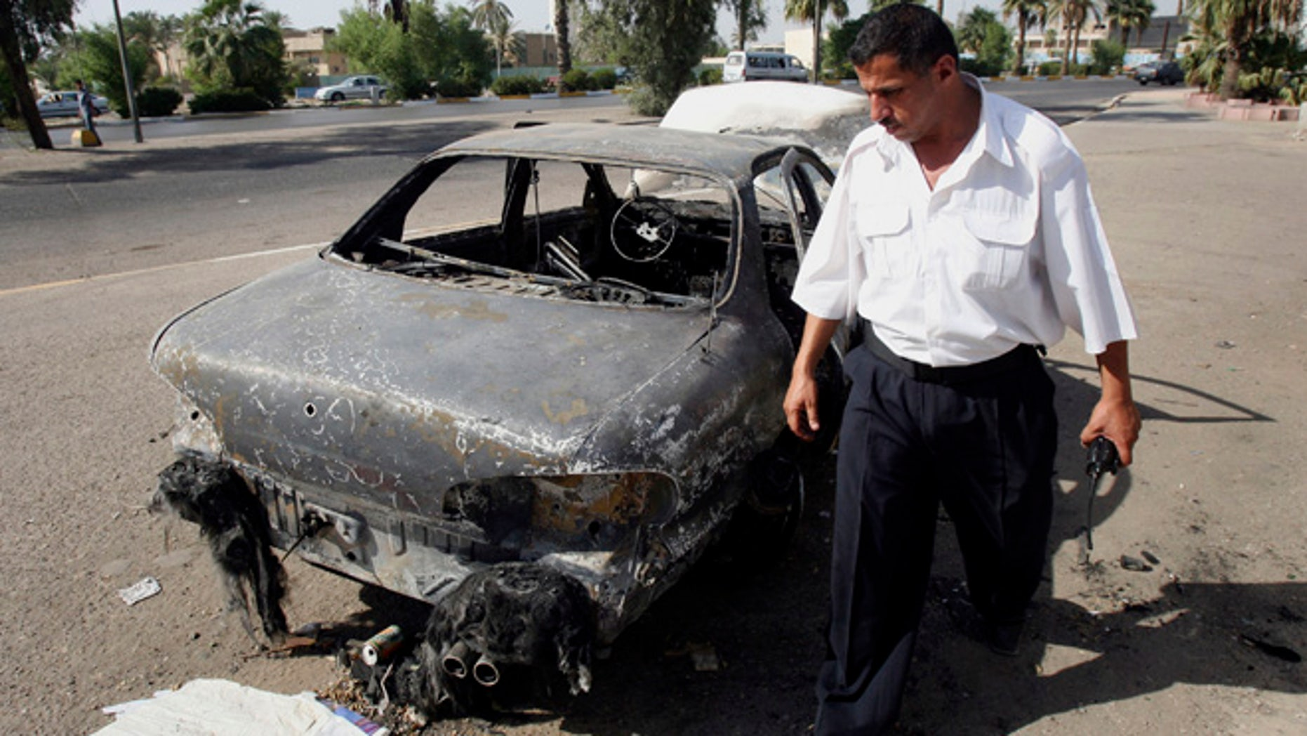 Sept. 25, 2007: An Iraqi traffic policeman inspects a car destroyed by a Blackwater security detail in al-Nisoor Square in Baghdad, Iraq.