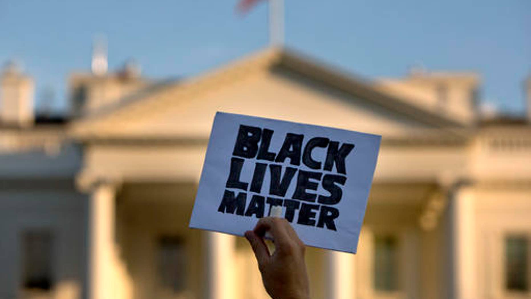 """A man holds up a sign saying """"Black Lives Matter"""" during a protest of shootings by police, at the White House in Washington, on July 8, 2016."""