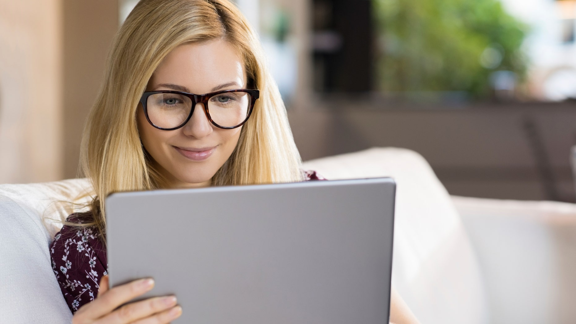 Happy young blonde woman sitting on sofa and using digital tablet. Happy young student with eyeglasses watching a movie on tablet. Female student studying on tablet at home.