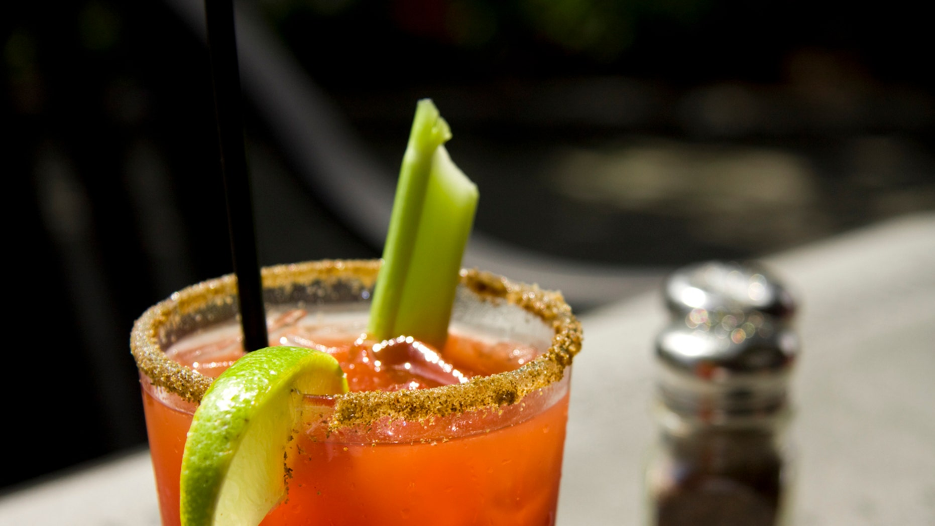 """""""Close up of a cool caesar or bloody mary cocktail drink rimmed with spice and garnished with lime wedge and celery stick. Shallow depth of field, good ad copy space."""""""