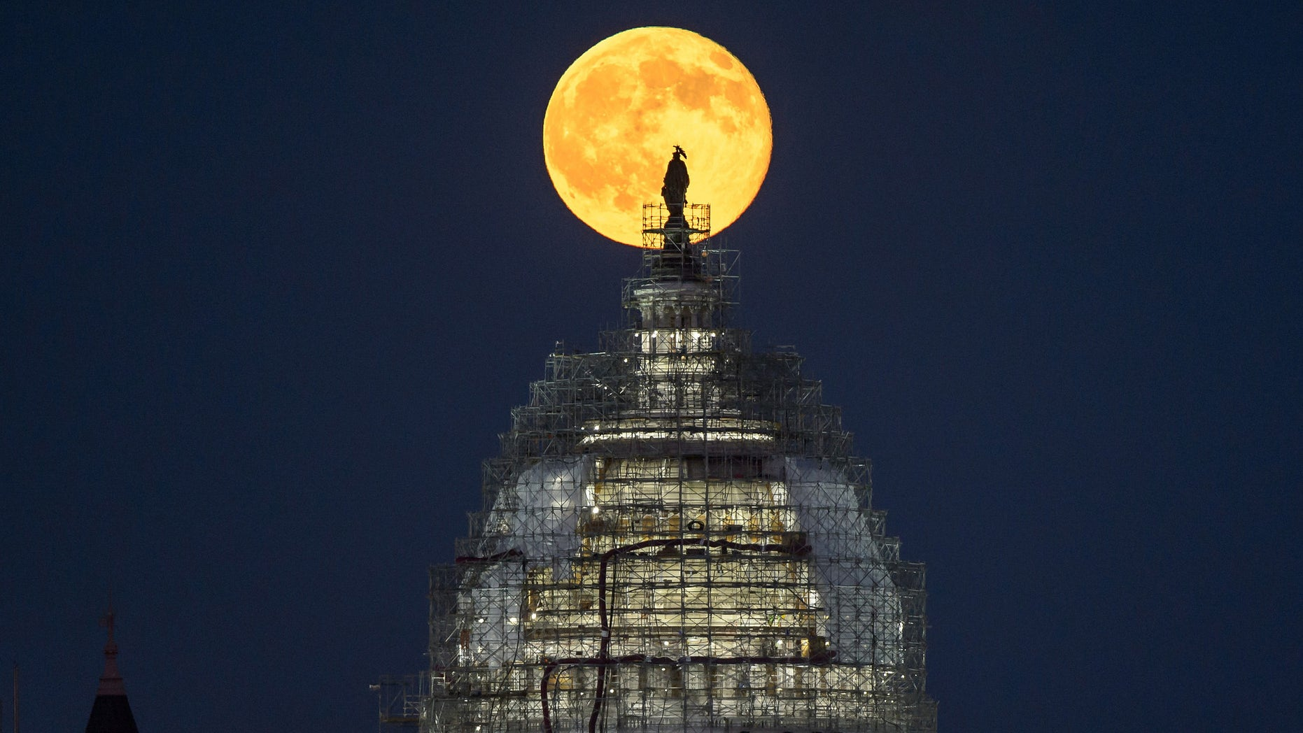 "The ""blue moon"" full moon of July 31, 2015 rises behind the dome the U.S. Capitol in this image from NASA photographer Bill Ingalls."