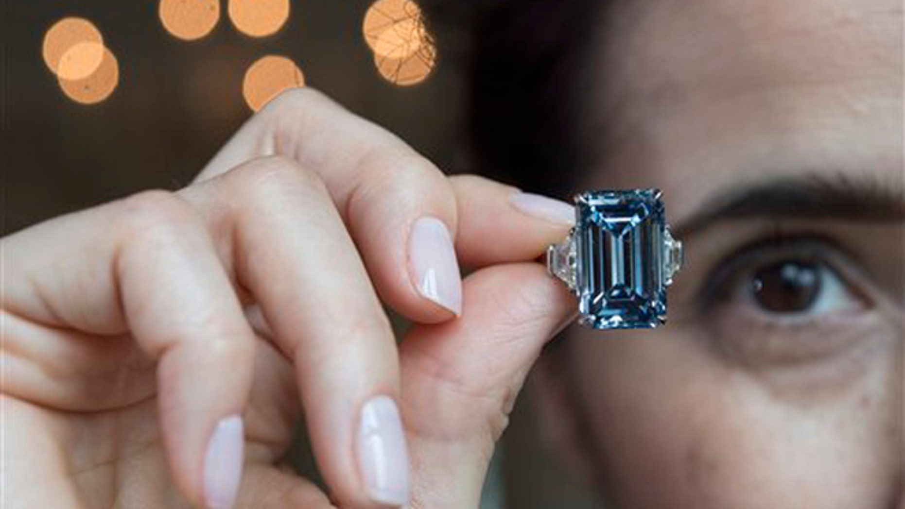 A Christie's employee holds Oppenheimer Blue diamond of 14.62 carats, which is estimated to be sold between 38,000,000 to 45,000,000 US Dollar, during a preview at the auction house Christie's, in Geneva, Switzerland, Thursday, May 12, 2016. The auction will take place on May 18, 2016 in Geneva. (Martial Trezzini/Keystone via AP)