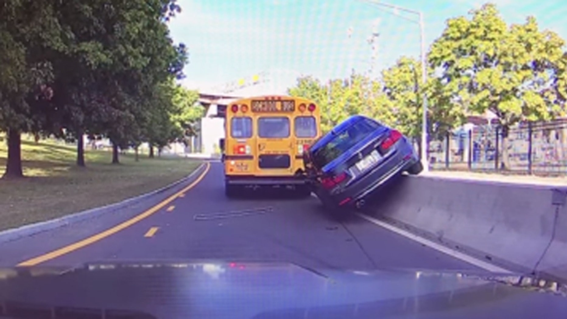 Video captured BMW crashing into construction barrier after nearly striking school bus. (WTEN-TV)
