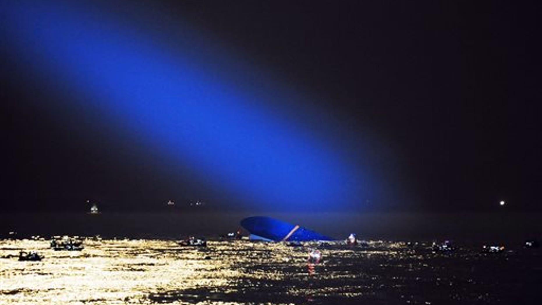 Blue search light cast by South Korean Coast Guard helicopter shows a sunken ferry in the water off the southern coast near Jindo, South Korea, Thursday, April 17, 2014. Fears rose Thursday for the fate of more than 280 passengers still missing more than 24 hours after their ferry flipped onto its side and filled with water off the southern coast of South Korea. (AP Photo/Yonhap)  KOREA OUT