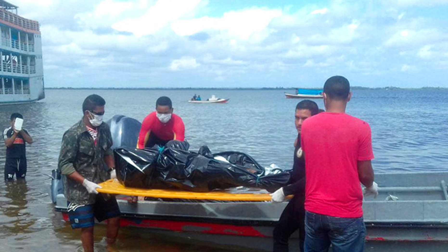 Rescue workers carry a body recovered from the Xingu River in this image released by Brazil's Secretary of Social Communication.