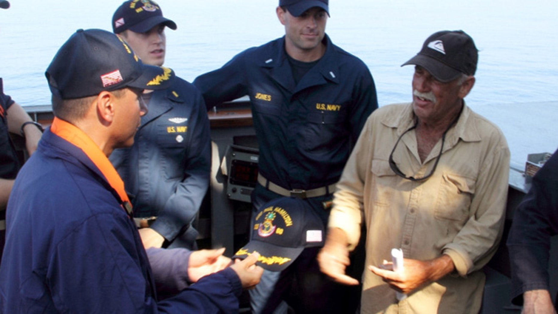 In this photo provided by the U.S. Navy, Cmdr. John Barsano, welcomes Ron Ingraham aboard the Arleigh Burke-class guided-missile destroyer USS Paul Hamilton after rescuing him  near Hawaii.