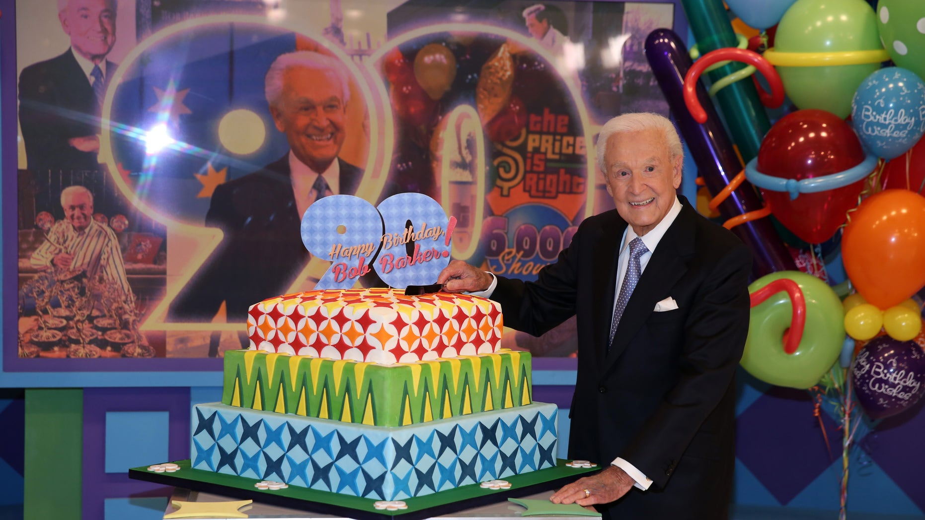 """November 5, 2013.  Bob Barker posing on the set of  """"The Price is Right"""" with a cake celebrating his 90th birthday at CBS Studios in Los Angeles. The veteran game show host, at the helm of The Price is Right from 1972 to 2007, was invited back by current host Drew Carey on Thursday, Dec. 12, to celebrate the milestone birthday."""