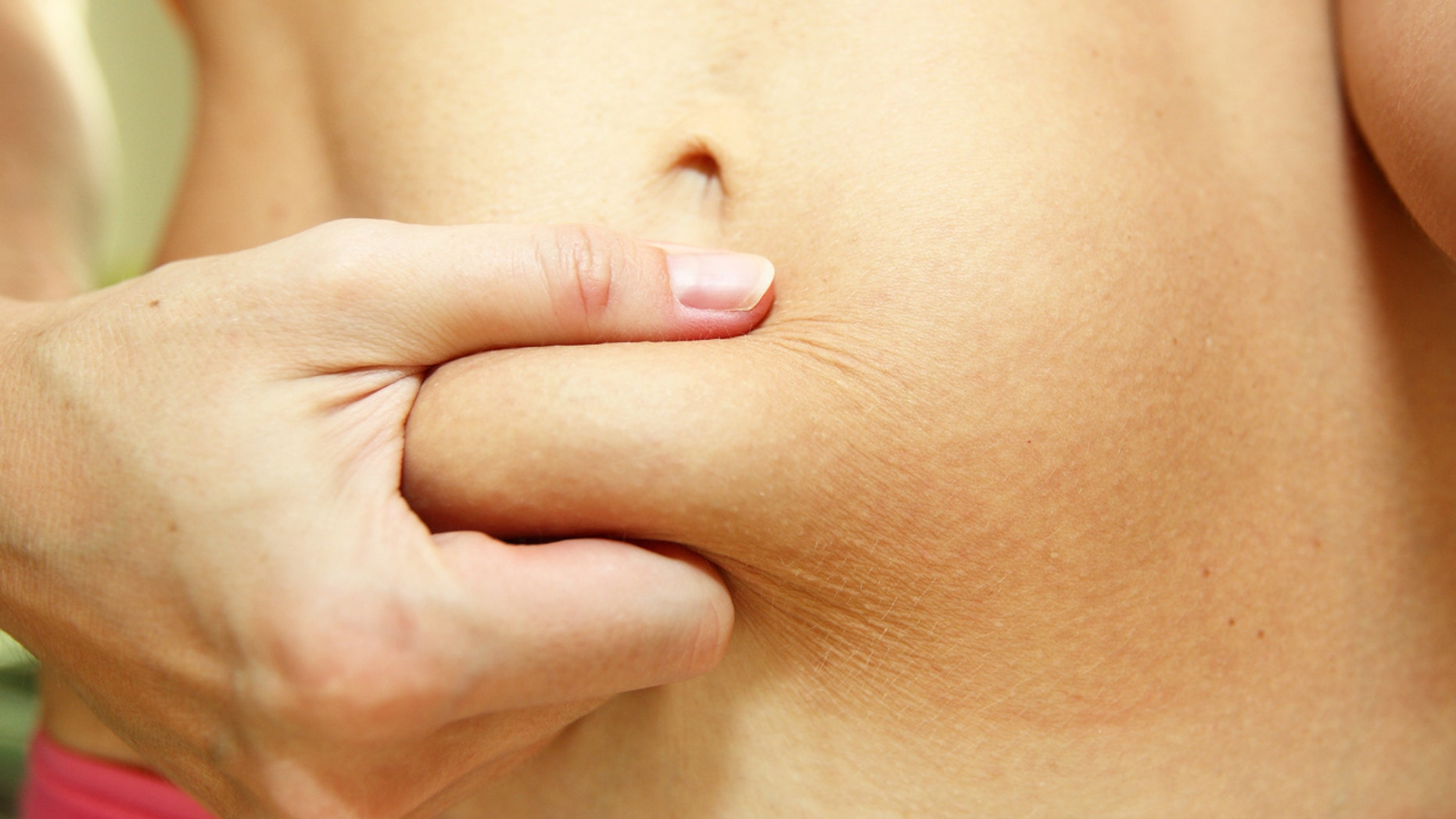 A close-up image of a slim young woman with a belly fat after giving