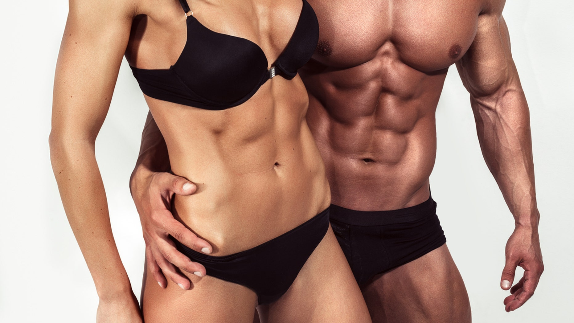 Bodybuilding. Strong man and a woman posing on white background in studio