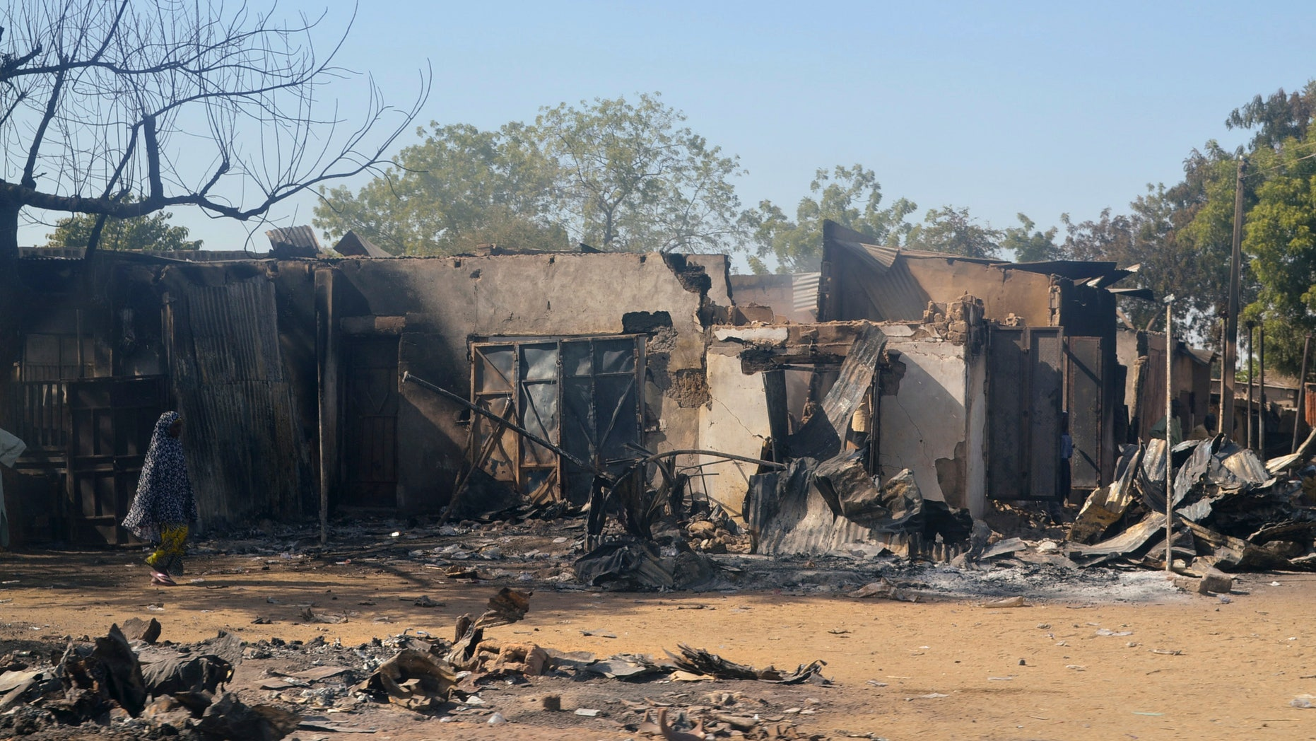 A woman walks past homes destroyed by the Islamist group Boko Haram in Bama, Borno State on Feb. 20, 2014.