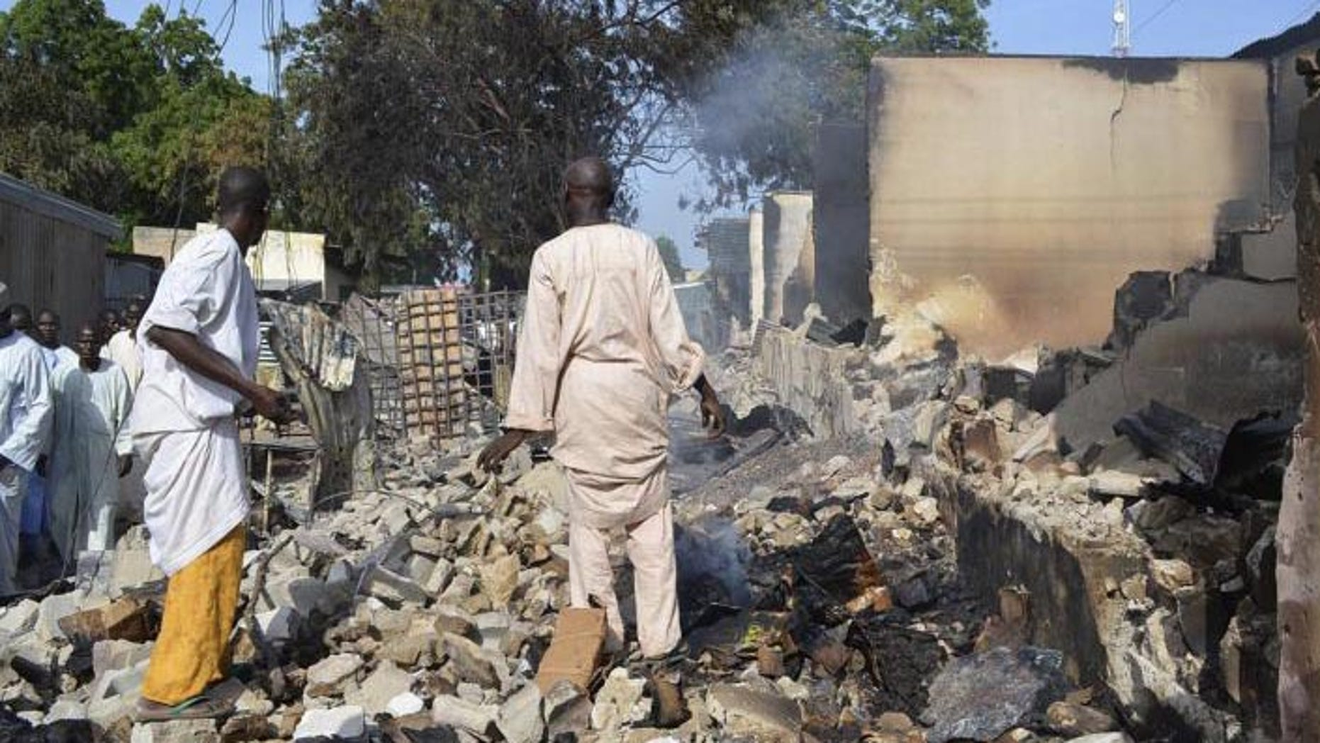 Residents watch as two men walk amidst rubble after Boko Haram militants raided the town of Benisheik in Nigeria. (Reuters)