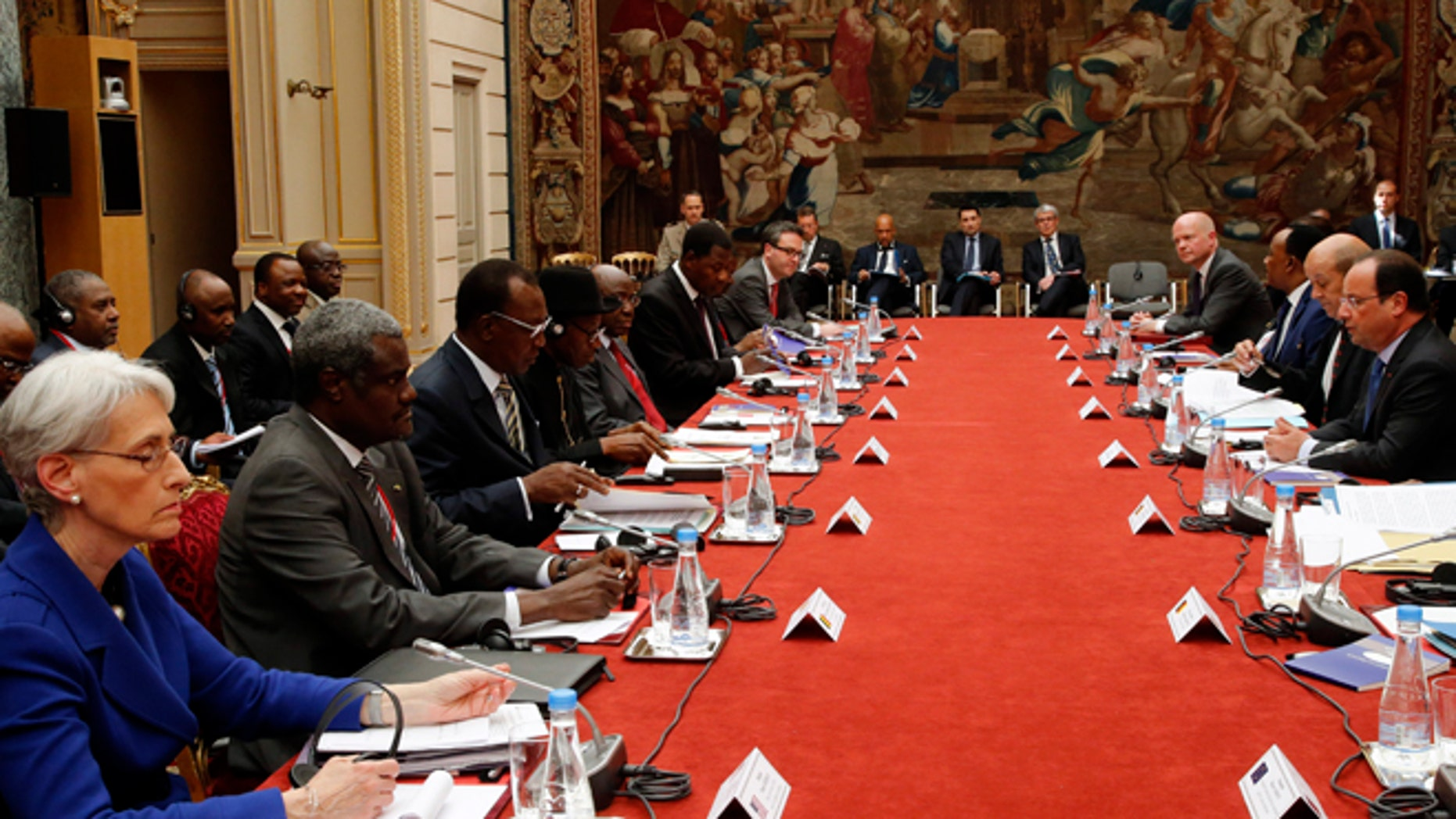 """May 17, 2014: U.S. Undersecretary of State for Political Affairs Wendy Sherman, left, looks on as French President Francois Hollande, right, talks during the round table photo session at the """"Paris' Security in Nigeria summit"""", at the Elysee Palace, in Paris."""