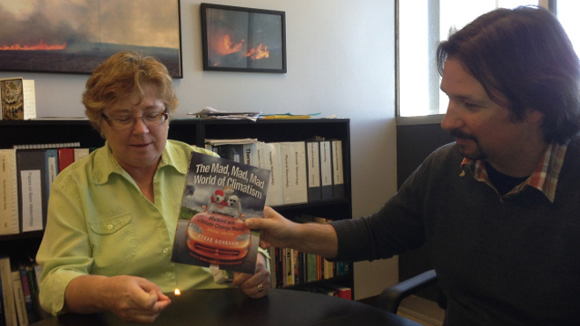 "San Jose State University's Dr. Alison Bridger holds a lit match beneath a book that claims global warming is ""natural"" as assistant professor Craig Clements looks on last month. The photograph has since been removed from the university's website. (SJSU.edu)"