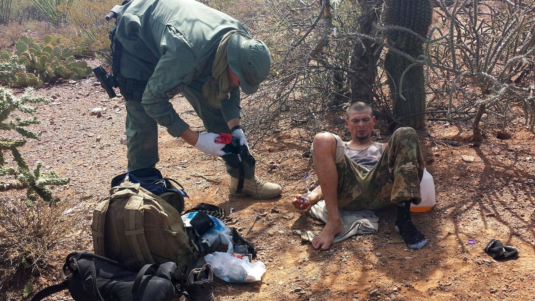 June 25, 2014:  An unidentified U.S. Border Patrol agent, left, helps an immigrant, including setting up intravenous fluid replacement for dehydration, near Sells, Ariz.