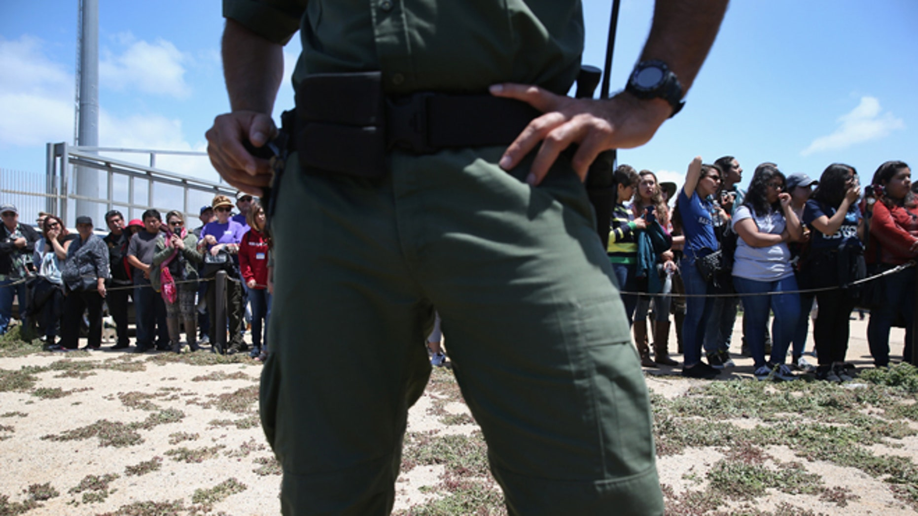 """SAN DIEGO, CA - APRIL 30:  A U.S. Border Patrol agent stands guard as families prepare to meet loved ones at the U.S.-Mexico Border fence during a """"Opening the Door of Hope"""" event on April 30, 2016 in San Diego, California. Five families, with some members living in Mexico and others in the United States, were permitted to meet and embrace for three minutes each at a door in the fence, which the U.S. Border Patrol opened to celebrate Mexican Children's Day. It was only the third time the fence, which separates San Diego from Tijuana, had been opened for families to briefly reunite. The event was planned by the immigrant advocacy group Border Angels.  (Photo by John Moore/Getty Images)"""