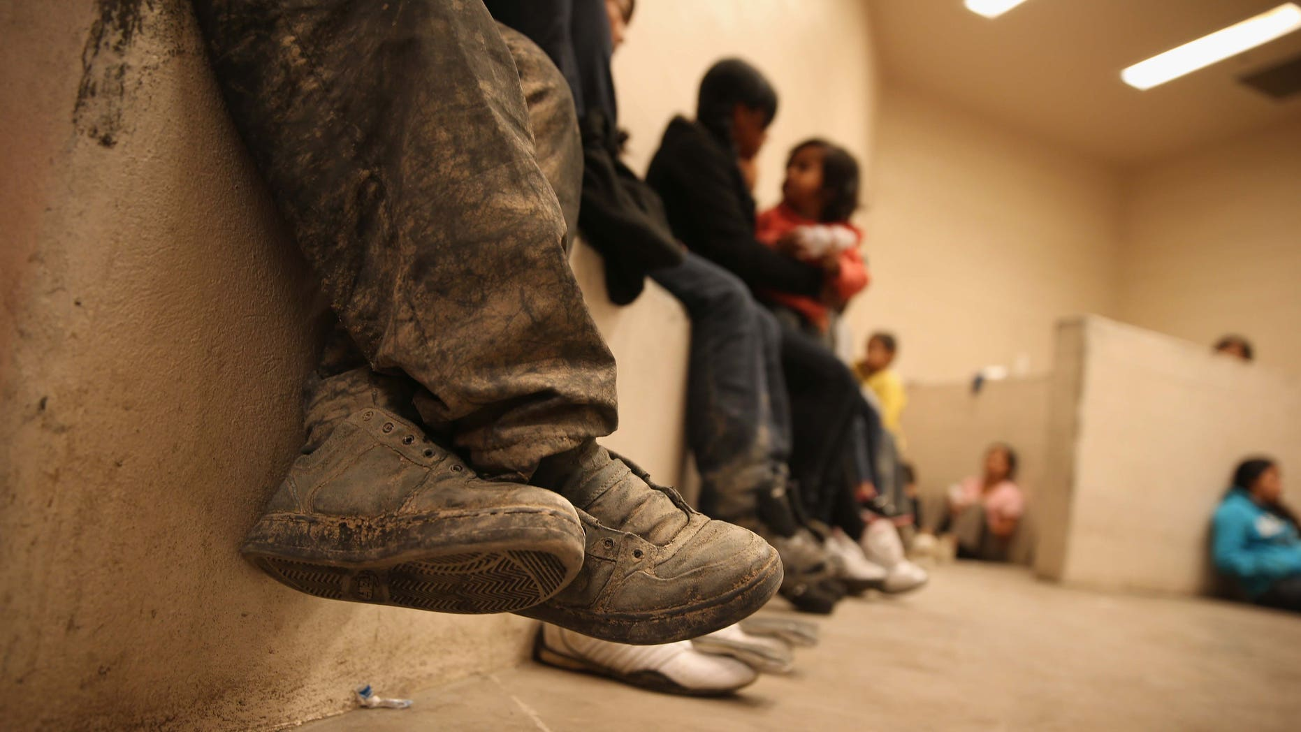 MCALLEN, TX - SEPTEMBER 08:  Women and children sit in a holding cell at a U.S. Border Patrol processing center after being detained by agents near the U.S.-Mexico border on September 8, 2014 near McAllen, Texas. Thousands of immigrants, many of them families and unaccompanied minors, continue to cross illegally into the United States, although the numbers are down from a springtime high. Texas' Rio Grande Valley area is the busiest sector for illegal border crossings into the United States.  (Photo by John Moore/Getty Images)