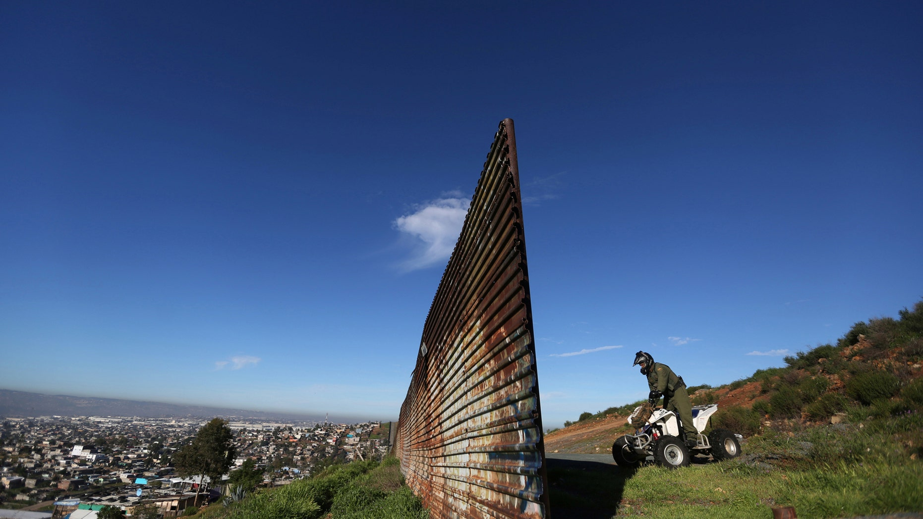 File photo: A member of the U.S. border patrol inspects the area where the border fence separating Mexico and the United States is interrupted, on the outskirts of Tijuana, Mexico, February 21, 2017. (REUTERS/Edgard Garrido)