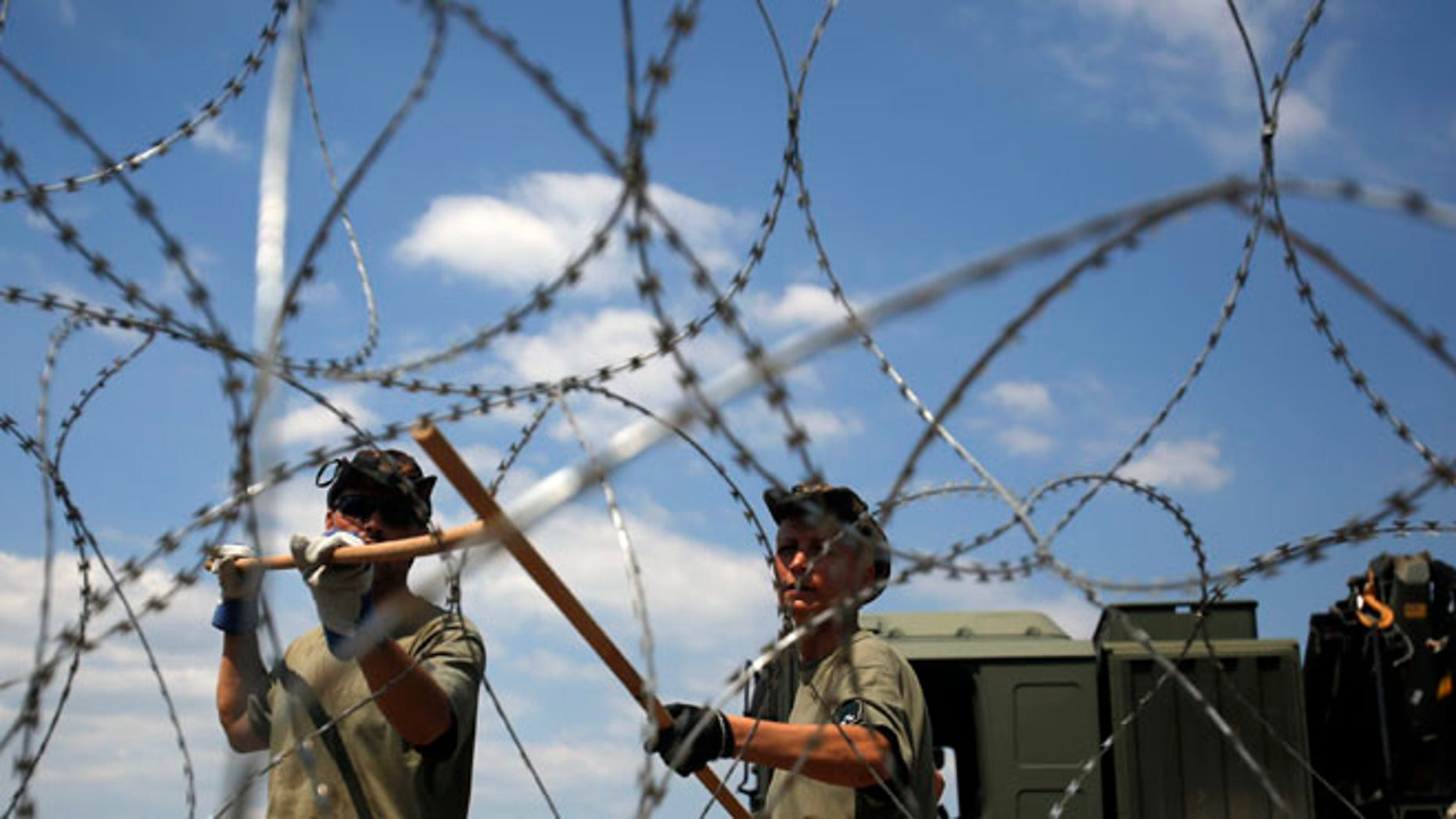 Hungarian soldiers place a barbed wire near Morahalom, Hungary.