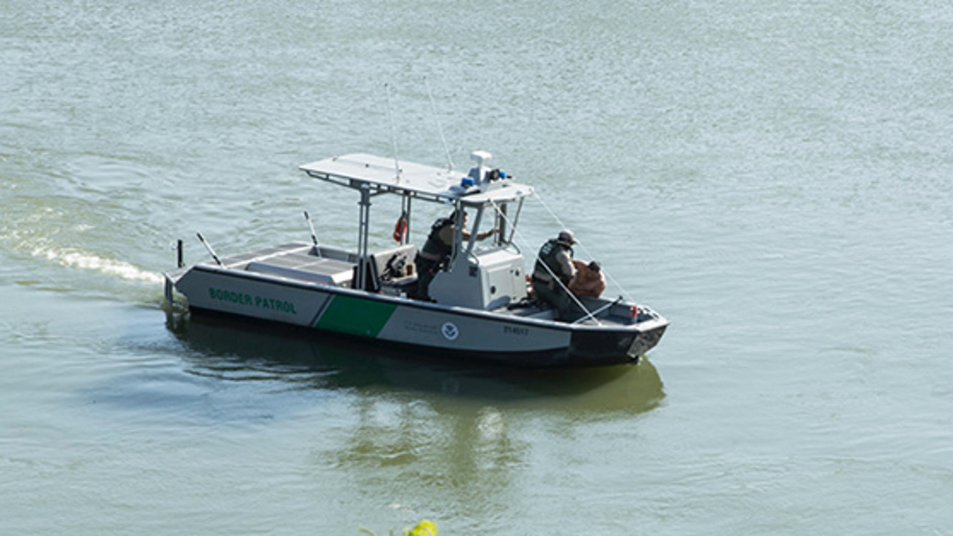 Border Patrol agents pull a man from the Rio Grande into their patrol boat near Roma, Texas Tuesday, April 18, 2017.