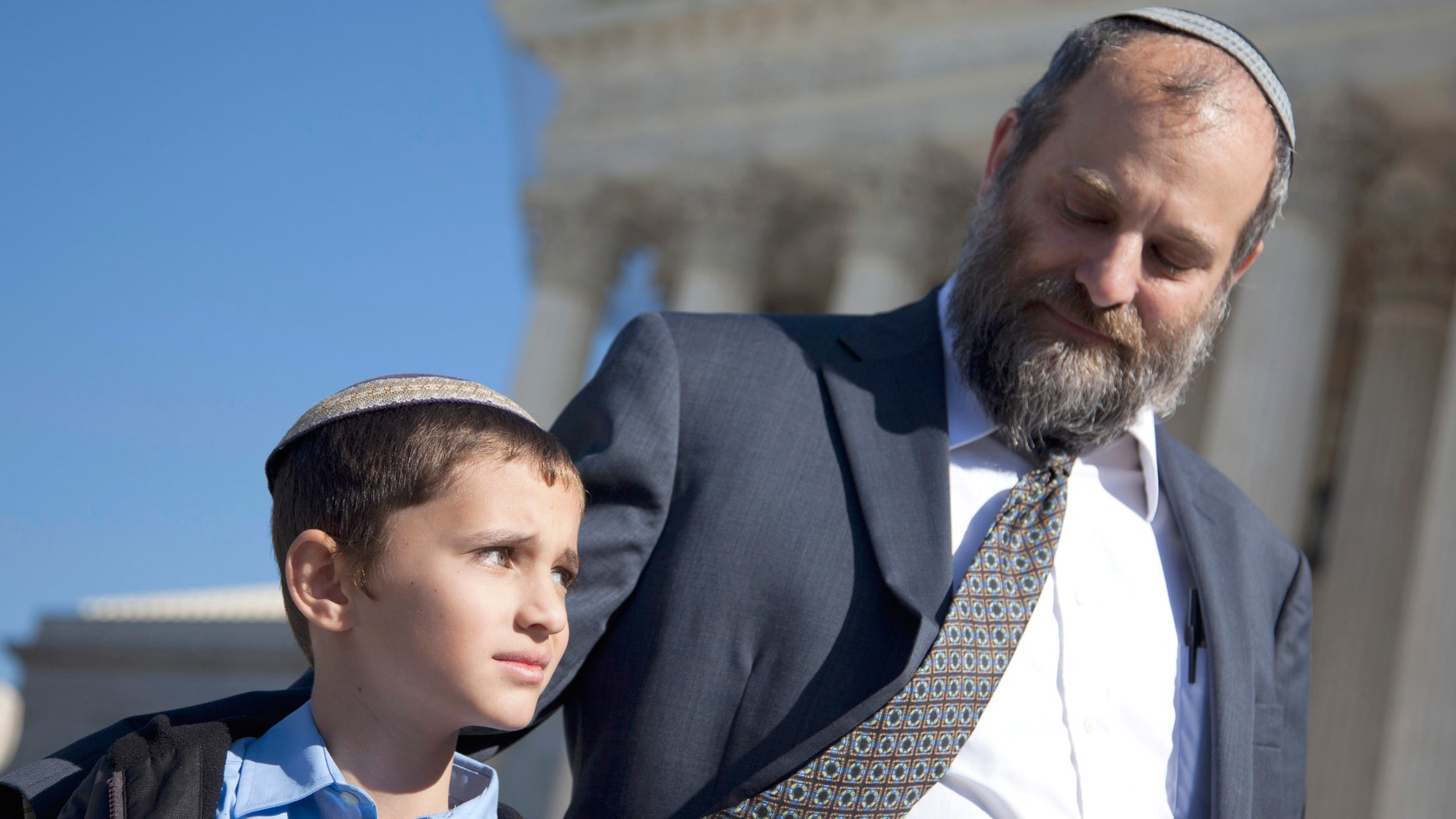 Nov. 7, 2011: Ari Zivotofsky, right, stands with his nine-year-old son, Menachem, outside the Supreme Court in Washington.