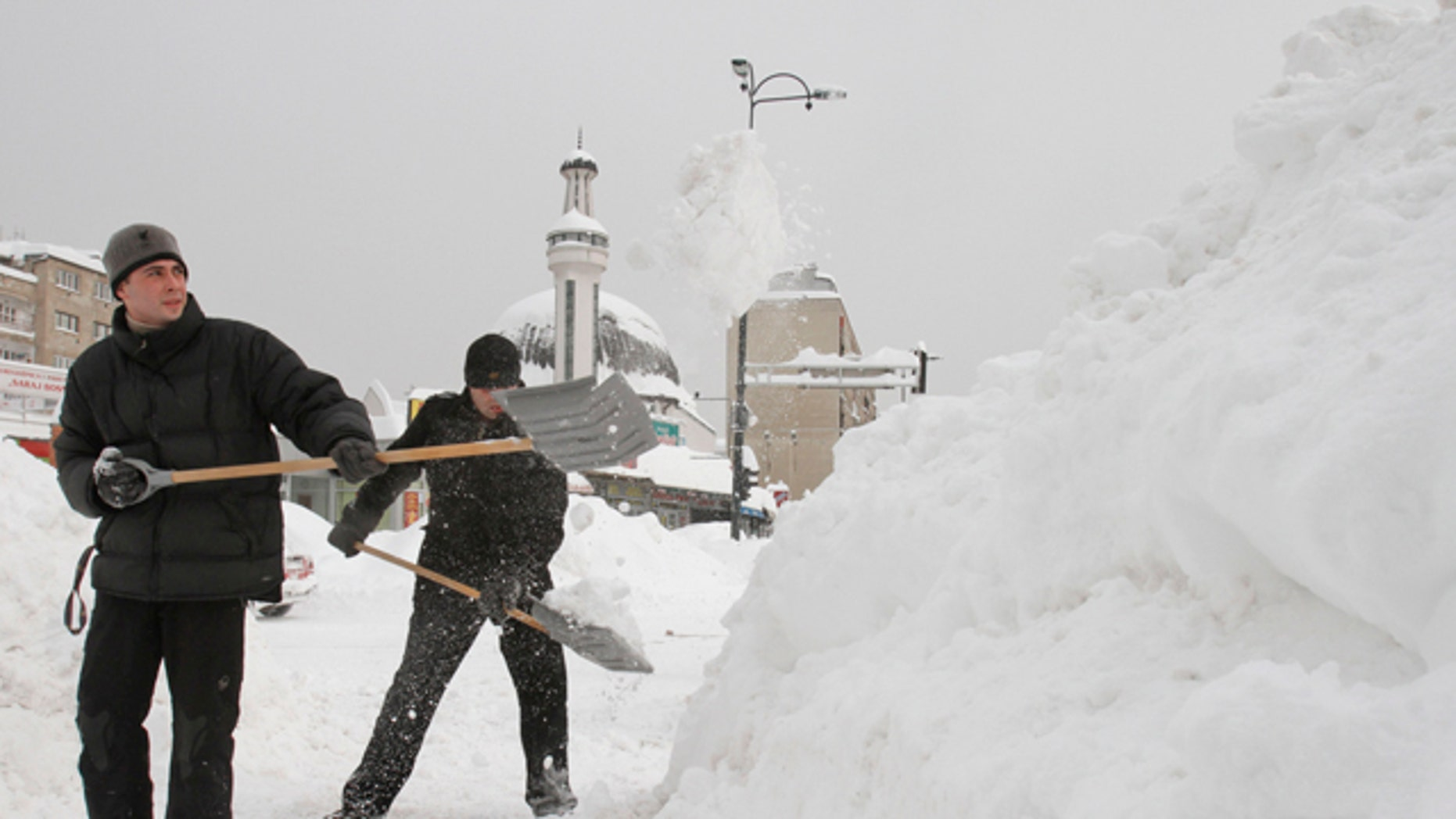 Feb. 4, 2012: Bosnian men shovel deep snow to clear the path for pedestrians, in the Bosnian capital of Sarajevo.