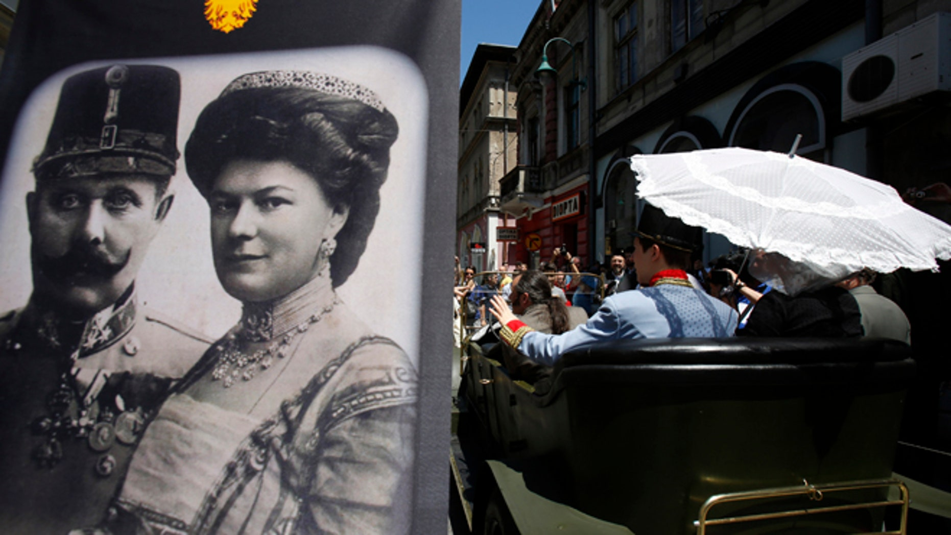 "June 28, 2014: Tourists pose for photos inside a replica of the ""Graf & Stift"" car, parked in front of a museum at the historical street corner in downtown Sarajevo, where Gavrilo Princip assassinated Austro-Hungarian heir to the throne Archduke Franz Ferdinand, in Sarajevo."