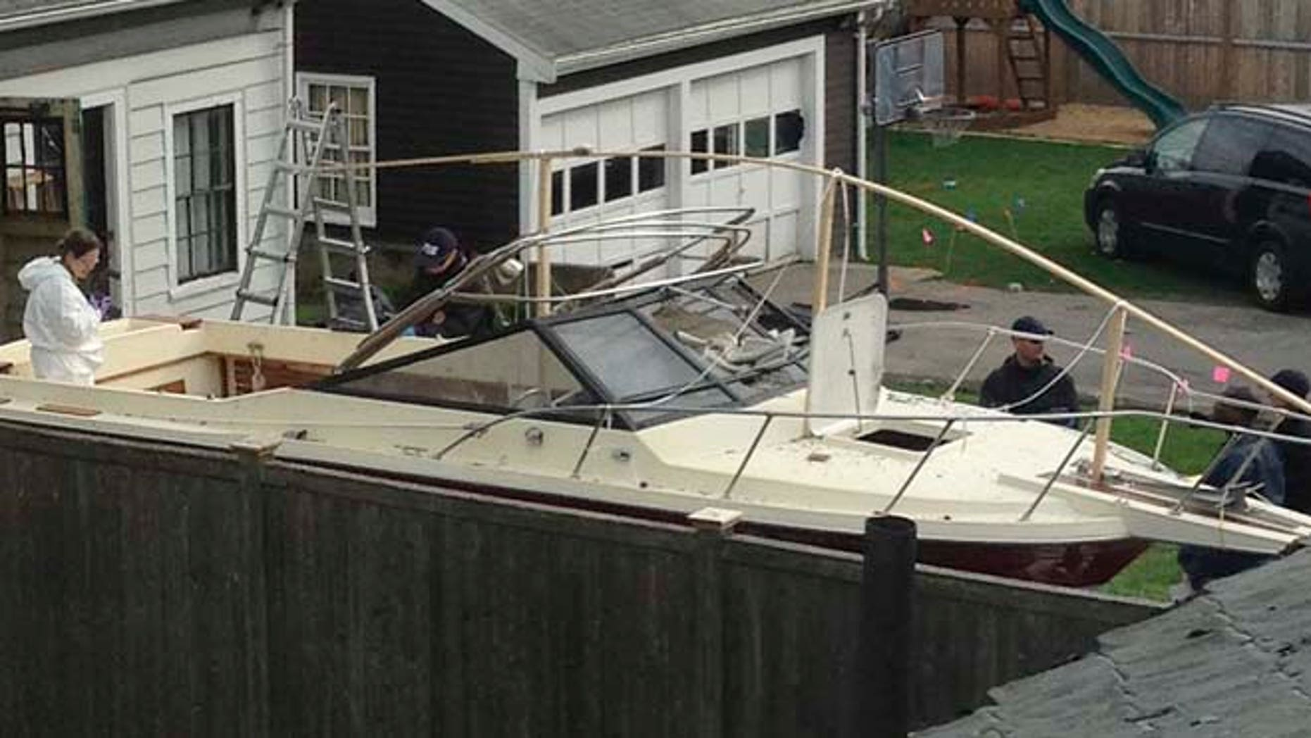 In this April 20, 2013 file photo, investigators work near the boat in Watertown, Mass., where the previous night police captured Dzhokhar Tsarnaev, the surviving Boston Marathon bombing suspect, after a car chase and gun battle earlier in the day left his older brother dead.