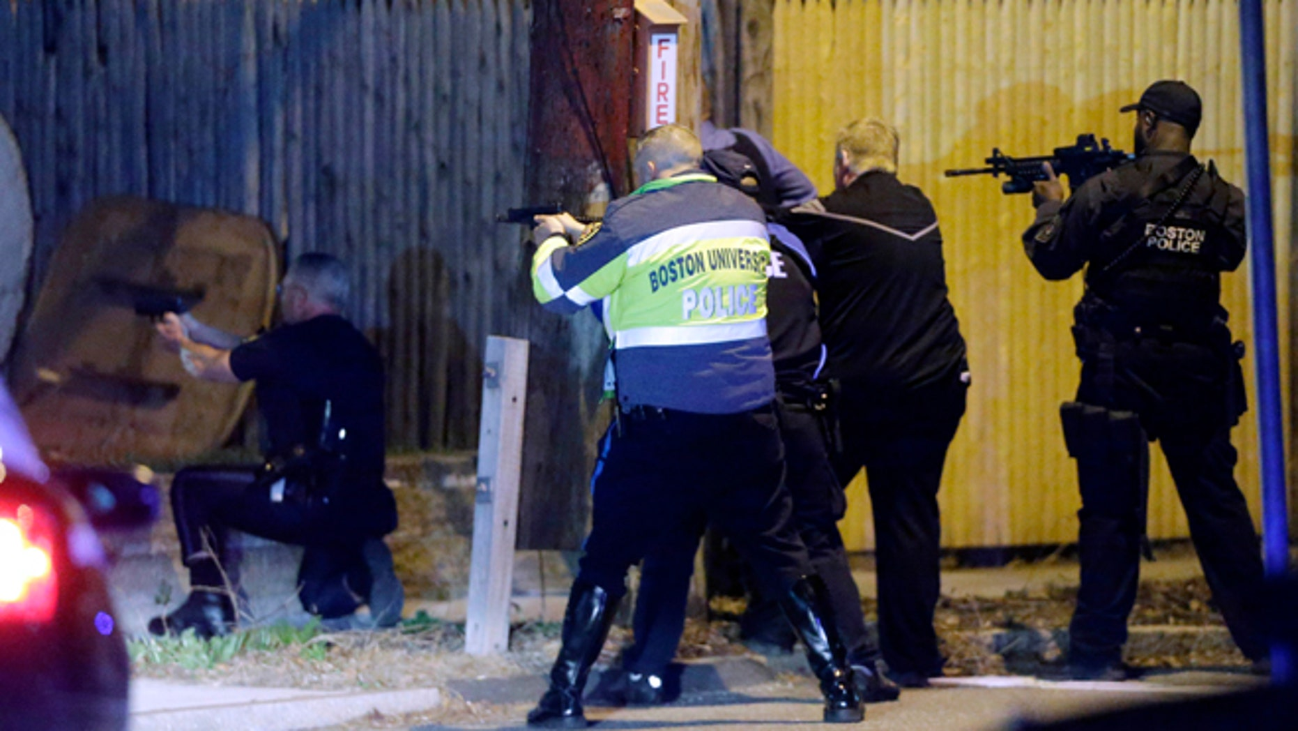 April 19, 2013. Police officers aim their weapons in a Watertown, Mass., neighborhood during a hunt for the Boston Marathon bombing suspects.