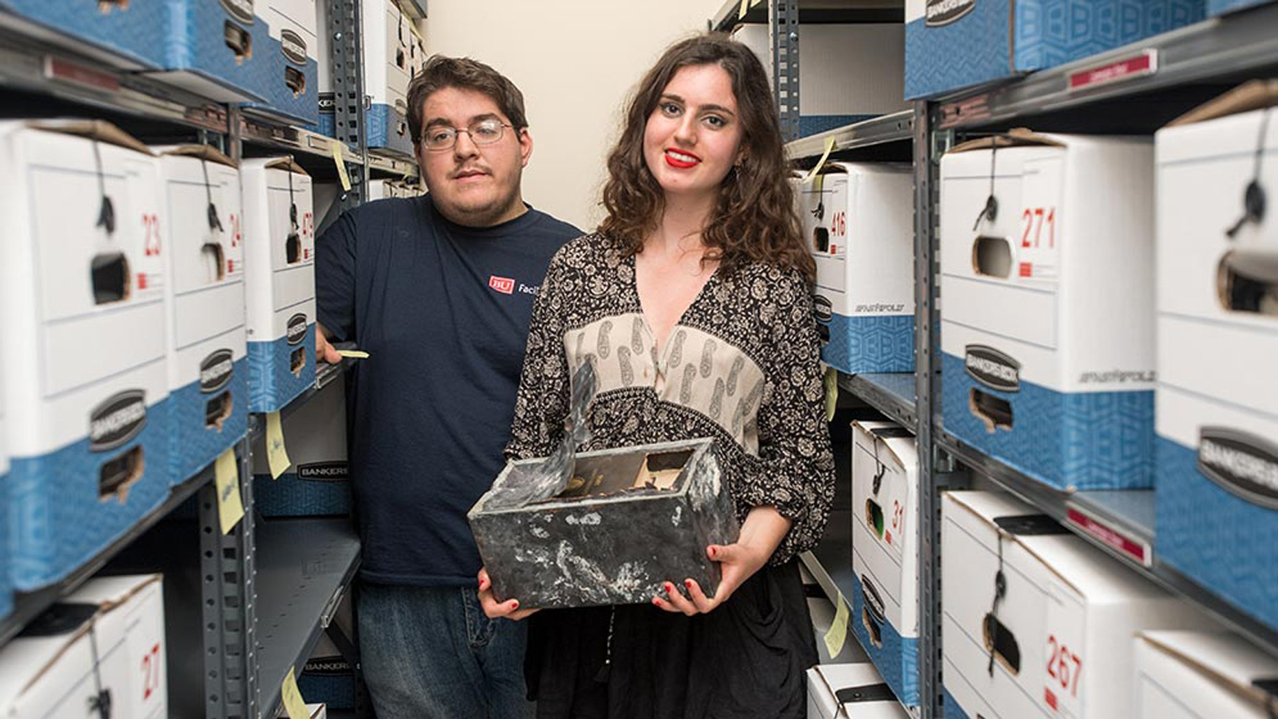 Adam Mumford (CAS'18) and Emma Purtell (CGS'17, COM'19) with the time capsule found in one of the hundreds of boxes of files they were archiving for BU's Facilities Management & Planning. Photo by Cydney Scott