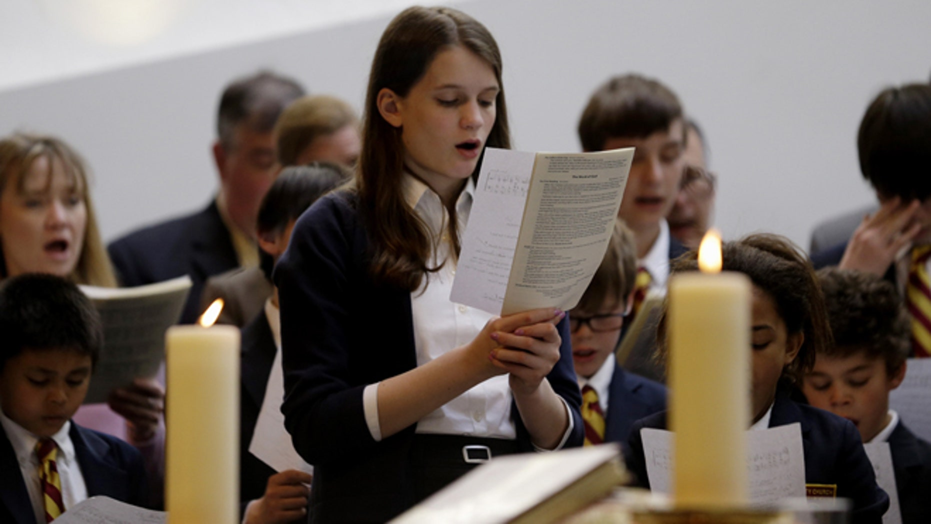 April 21, 2013: Annie Packard, 13, sings during Trinity Episcopal Church Sunday service at Temple Israel, which allowed the Trinity congregation hold service in Boston. Trinity is within the blocked-off area near the finish line of the Boston Marathon, where earlier in the week two bombs exploded. Packard was in the grandstands when the first bomb exploded and ran away in the direction of the second bomb, which went off 10 seconds later.