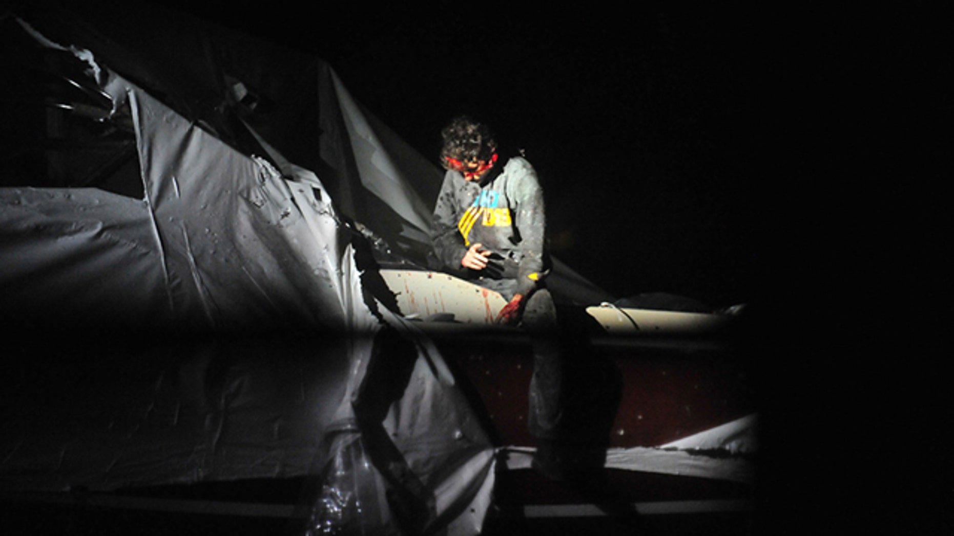 April 19, 2013: In this photo provided by the Massachusetts State Police, Boston Marathon bombing suspect Dzhokhar Tsarnaev leans over in a boat at the time of his capture by law enforcement authorities in Watertown, Mass.